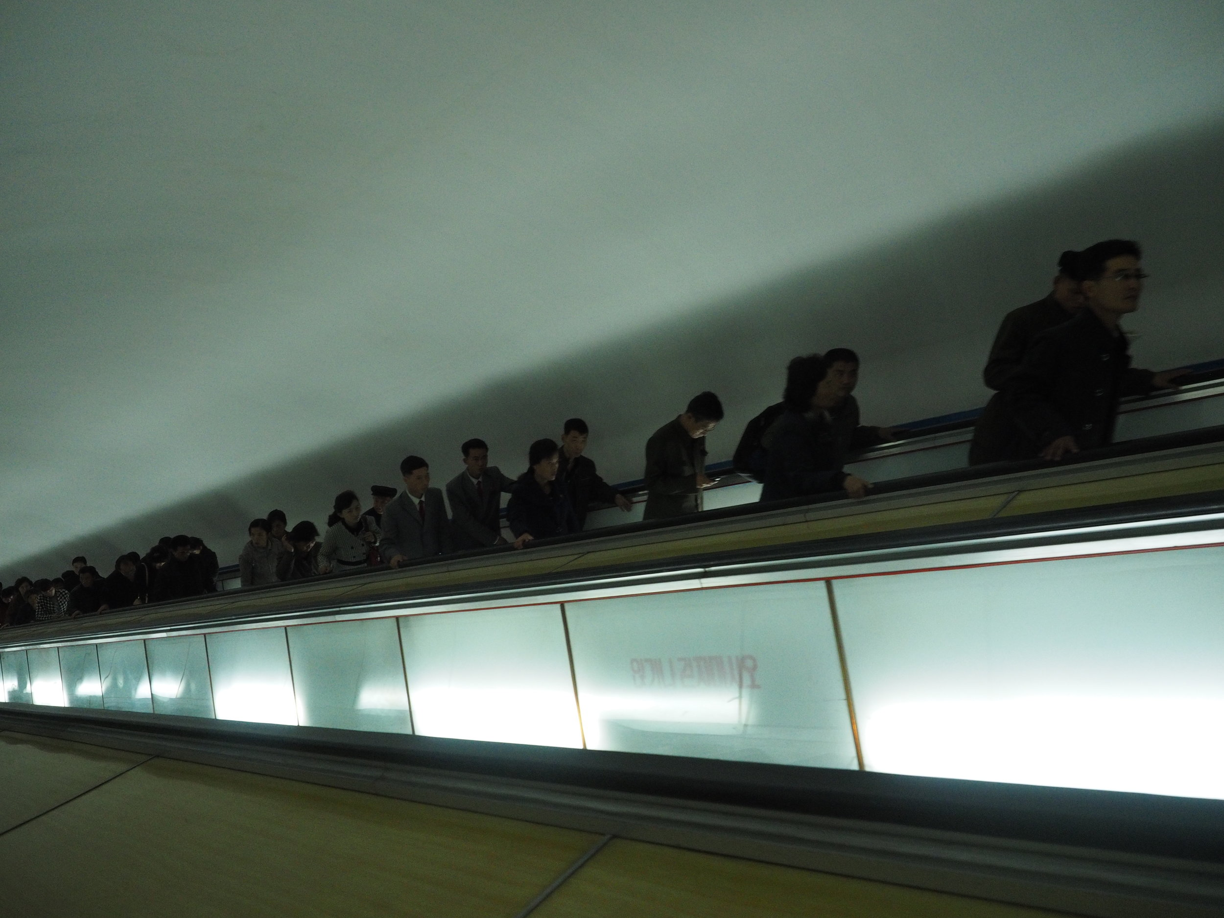Faceless commuters leave the Pyongyang metro.