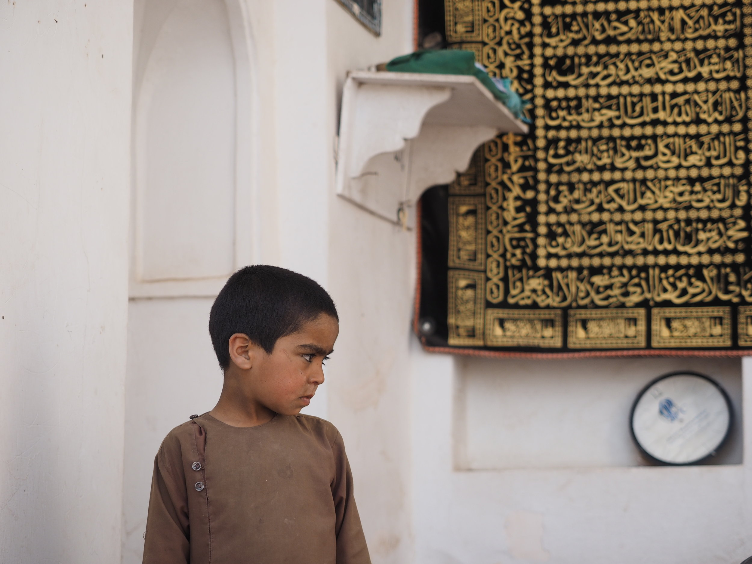 A child begging outside a mosque.