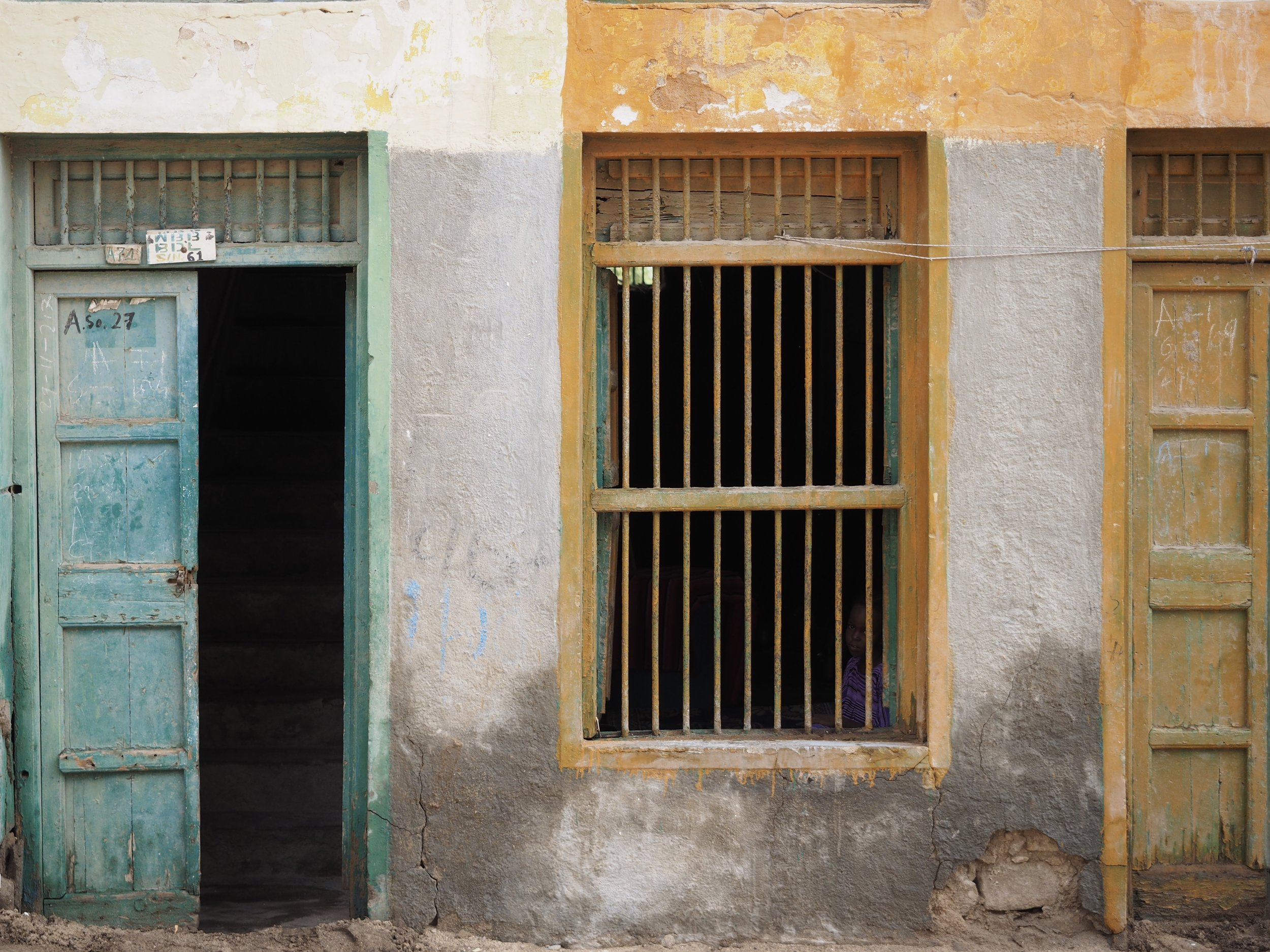 A child keeps a safe distance behind bars in Berbera.