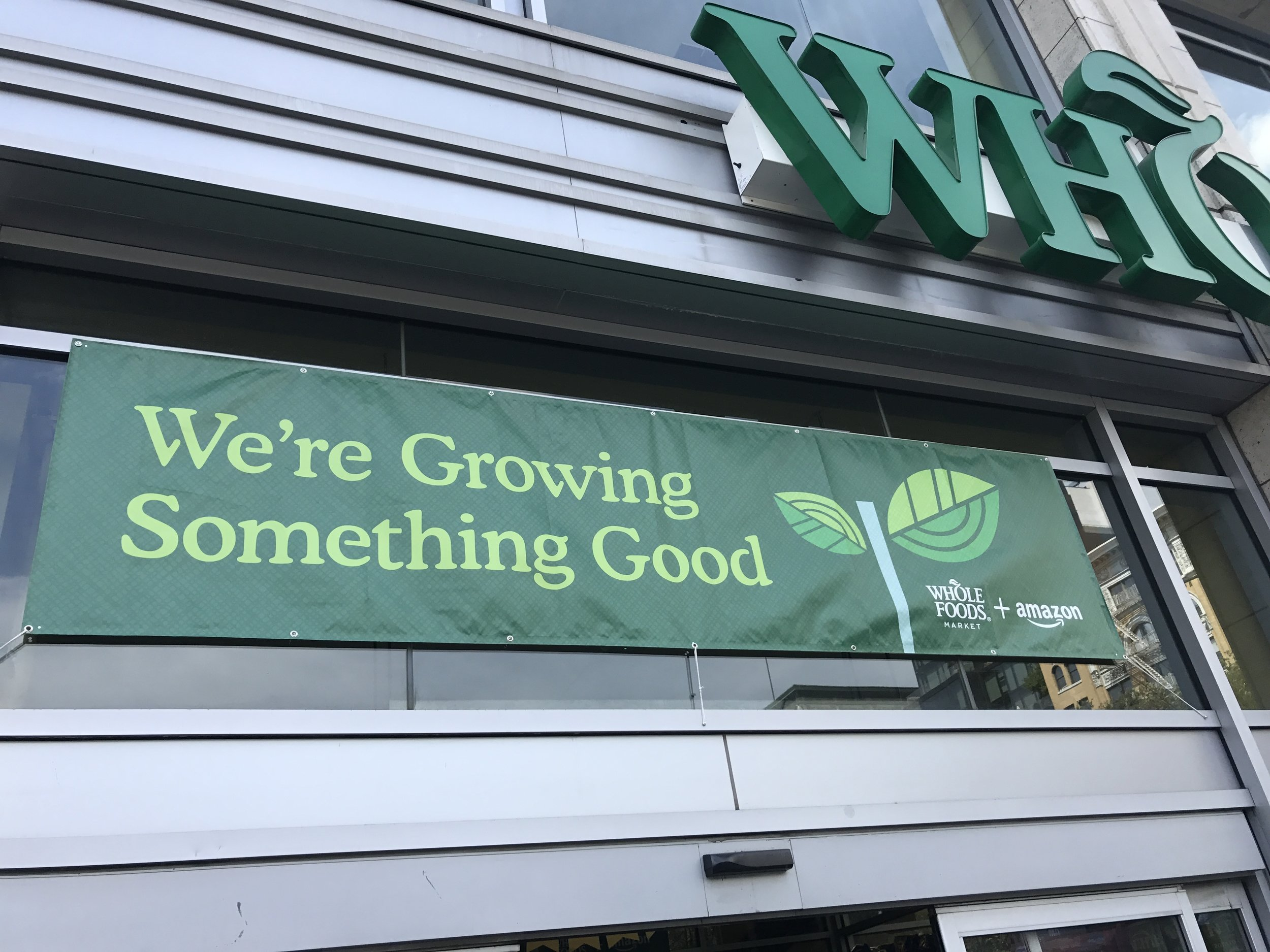 New sign hangs over the Union Square Whole Foods announcing the completed merger with Amazon.