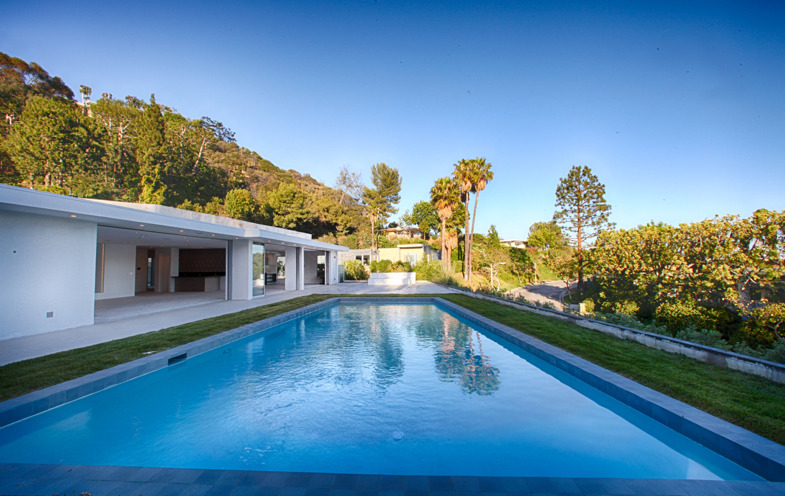 DABNEY LANE | BEVERLY HILLS   This contemporary construction fits into the hillside with a streamlined minimalist frame. Indoor/outdoor design + pocket doors set the scene for timeless California living.