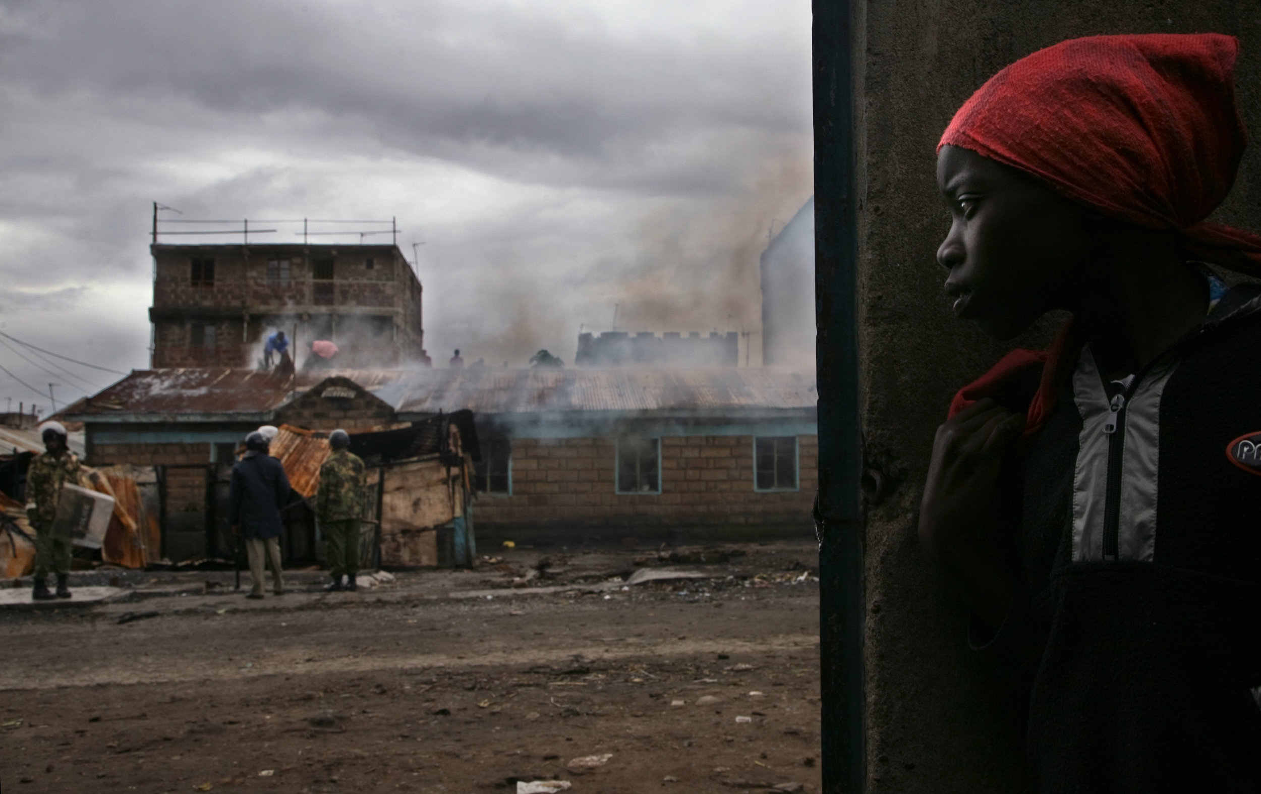 Police and residents try to quell a fire set in the Mathare slum in Nairobi as ethnic violence rages on.