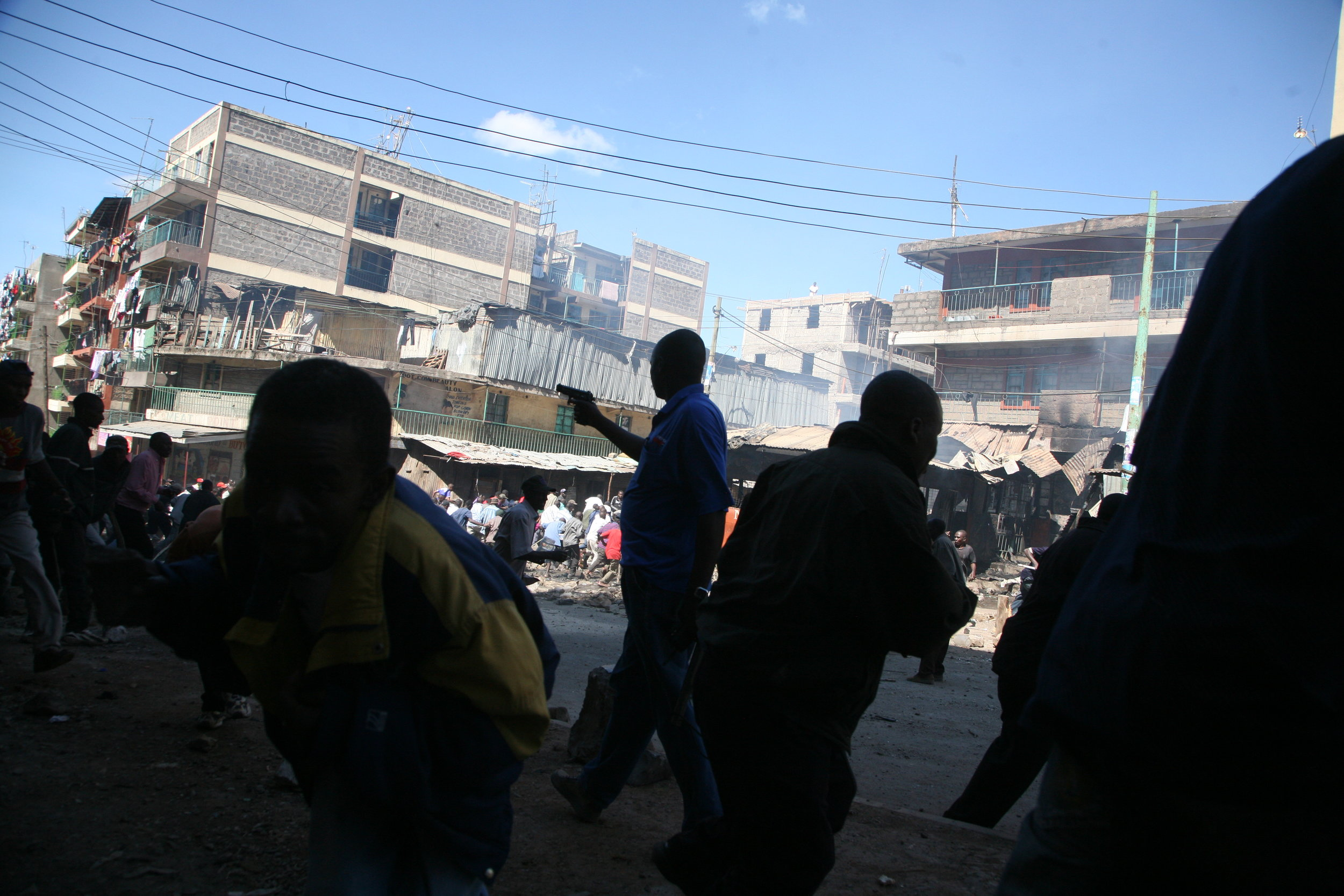 Protestors take cover as an undercover police officer pulls out a hand gun during clashes between rival ethnic groups in the Mathare slum.