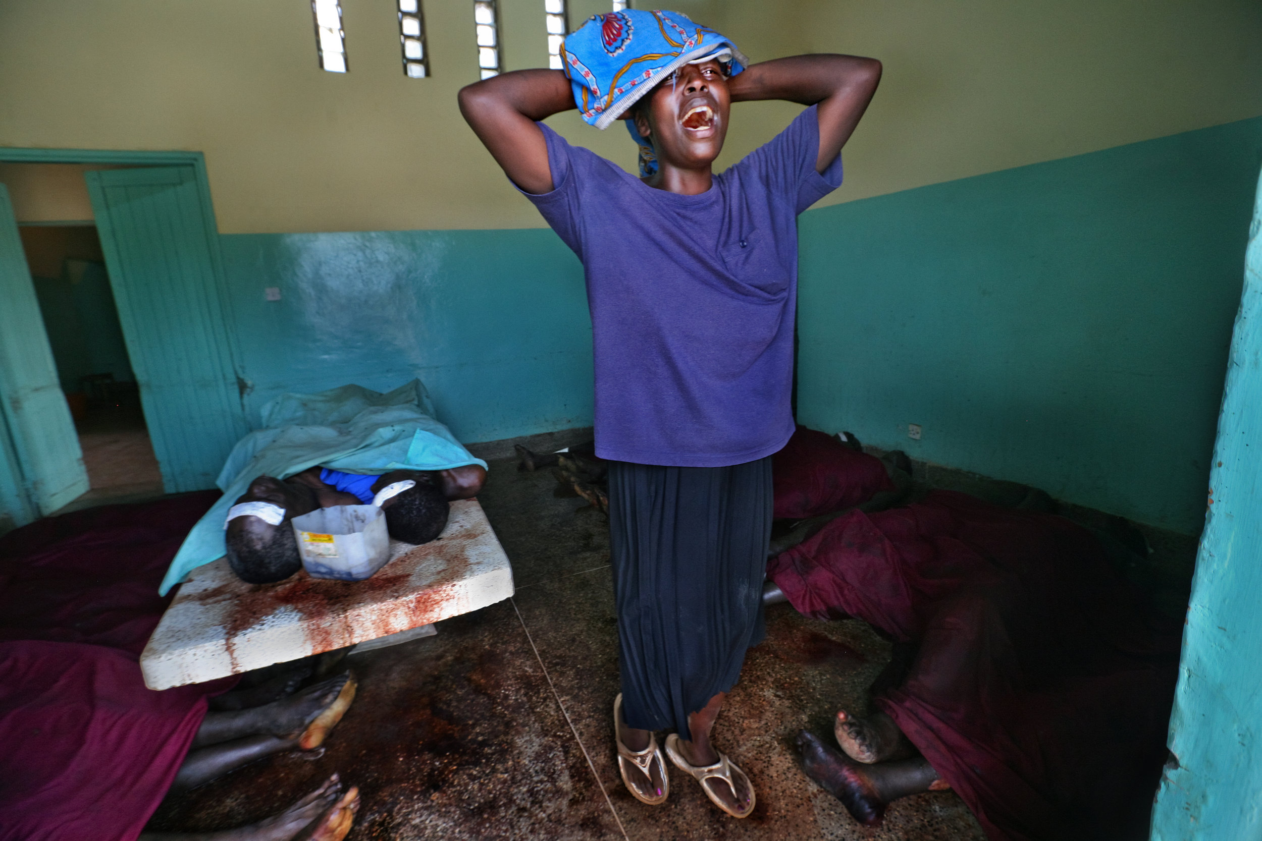 A woman cries as she searches unsuccessfully for a missing relative among the bodies laid out in the overflowing morgue in Kisumu.