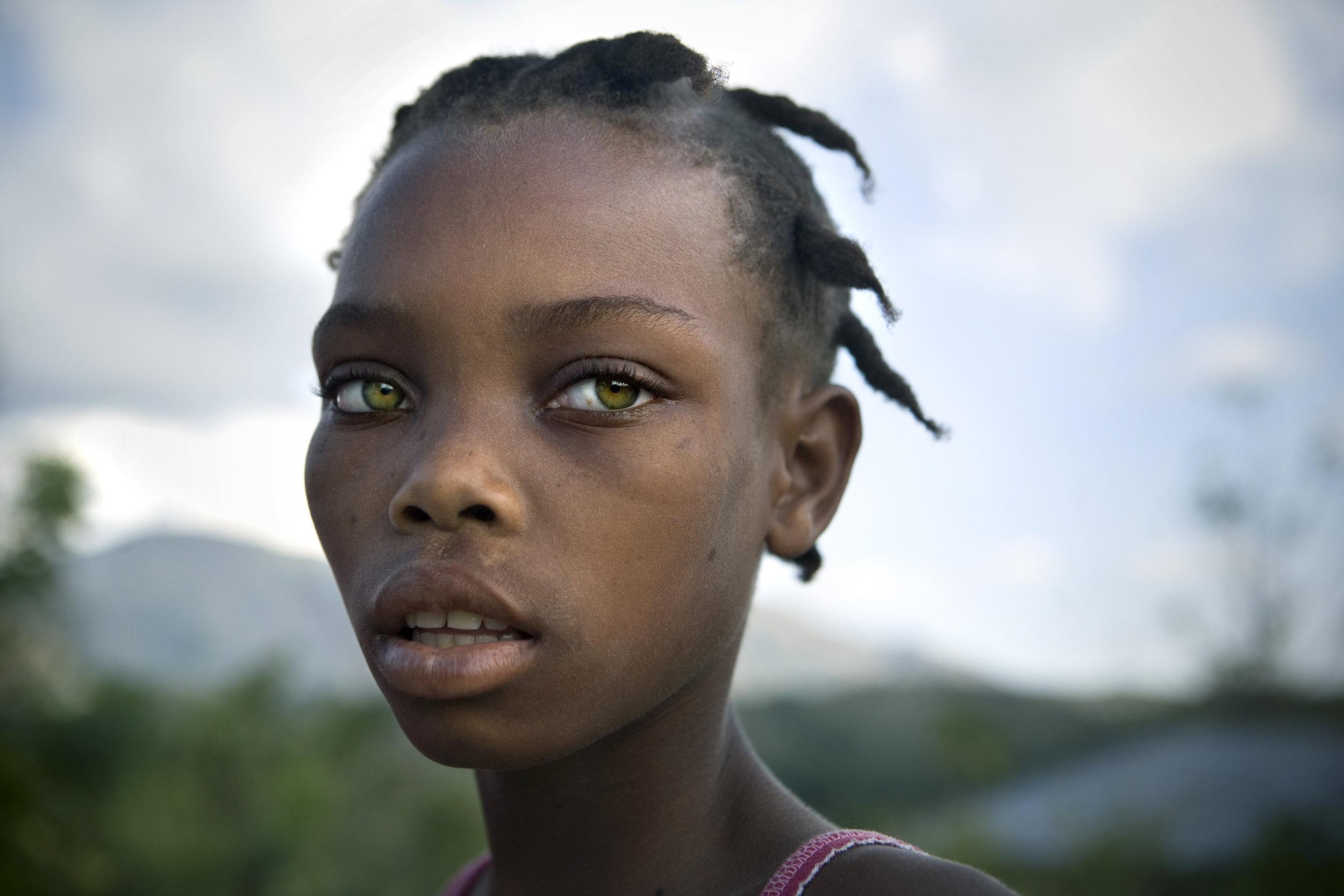 Jenny Duqai, 12, outside her home in Gros-Morne, Haiti.