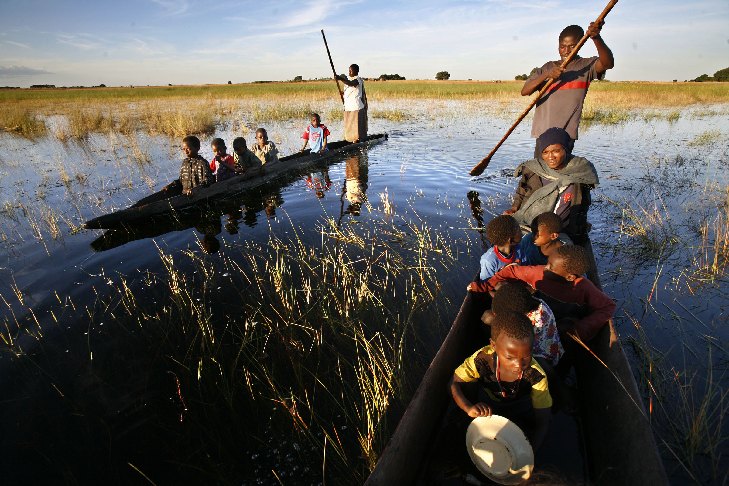 Munalula, 8, sits in the front of a dugout canoe with her lunch bowl, as she and her classmates are carried to school across the flood plains at sunrise. The school receives rations from the United Nations World Food Program to the students who are vulnerable to food insecurity in Mulondo Village, Zambia.