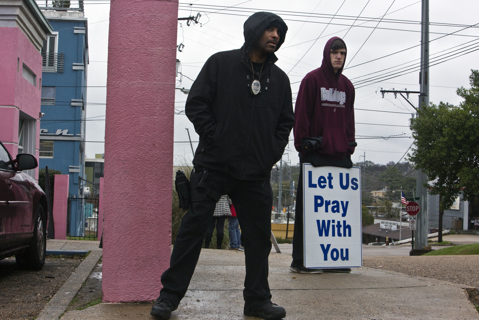 The security guard at the Jackson Women's Health Organiztion, watches a woman walk towards the clinic, the only abortion clinic in the state of Mississippi, while an anti-abortion demonstrator prays outside.