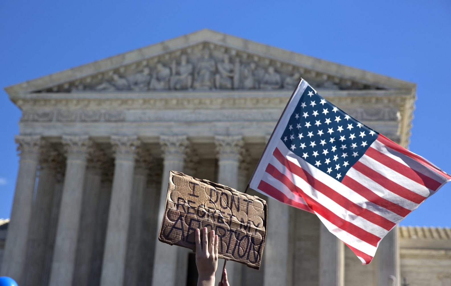 Pro-choice demonstrators hold signs during a rally outside the Supreme Court after the court struck down Texas' abortion restrictions as placeing an undue burden on a woman's constitutional right to an abortion.