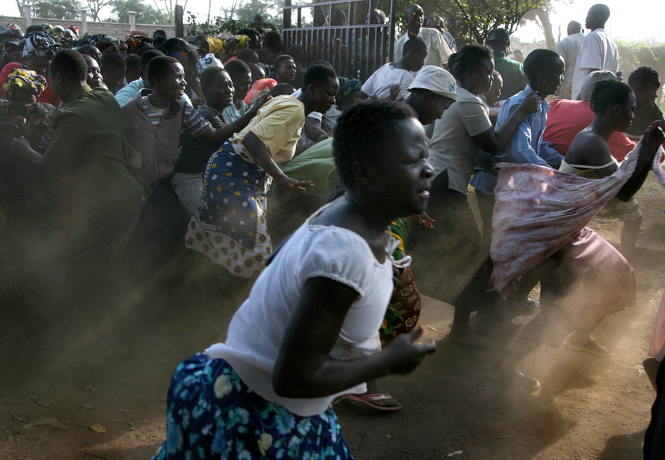 Desperate residents of Mathare break through the fence at the area chief's office and make a dash towards food stocks being handed out during a food distribution by the Kenyan Red Cross. They were chased back by police with whips.