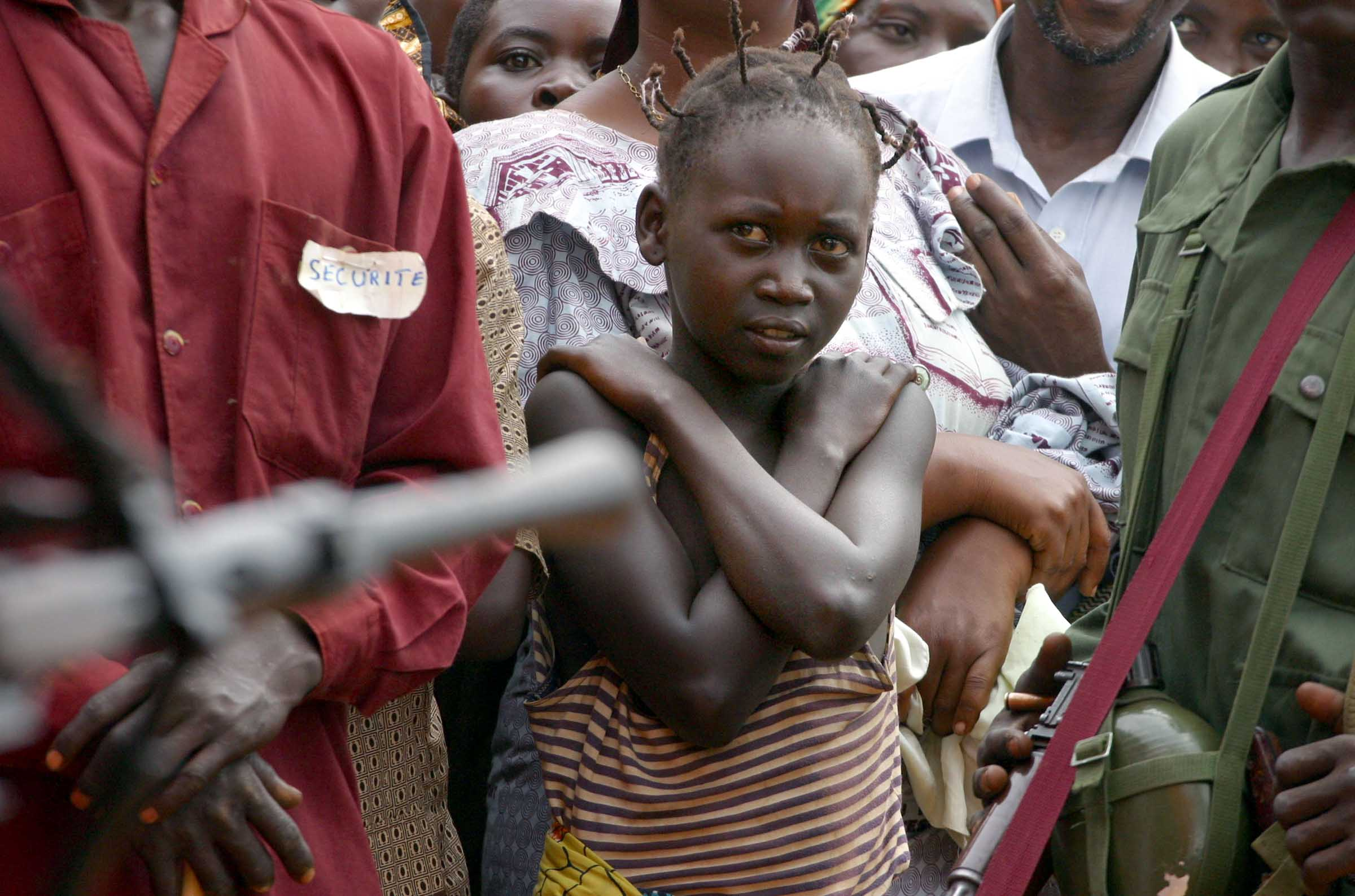 A young girl watches a rally for UPC president Thomas Lubanga, guarded by UPC soldiers in the village of Iga Barriere in Eastern Democratic Republic of Congo.