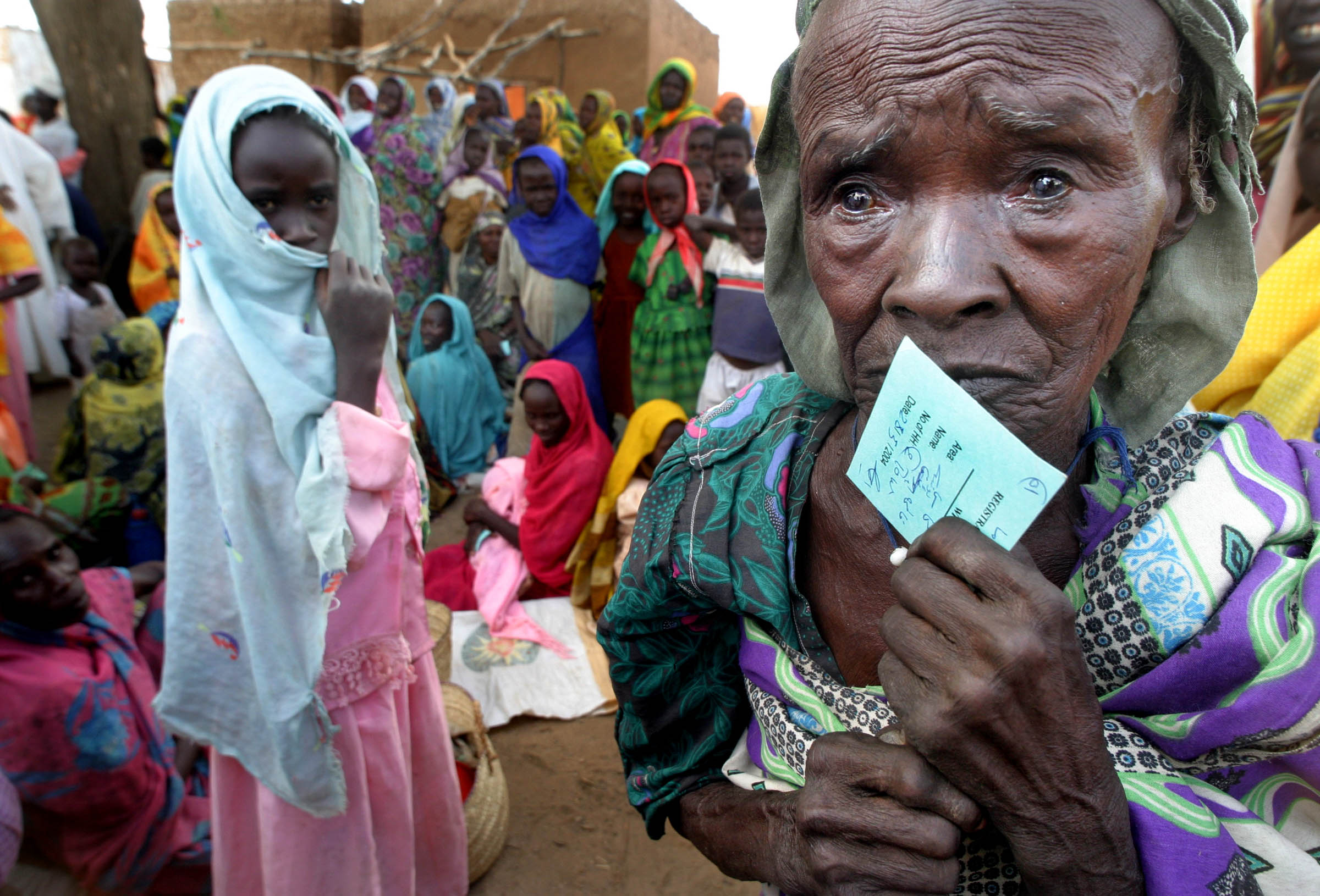 An elderly displaced woman holds her ration card as she waits to receive food in Niyama, Darfur.