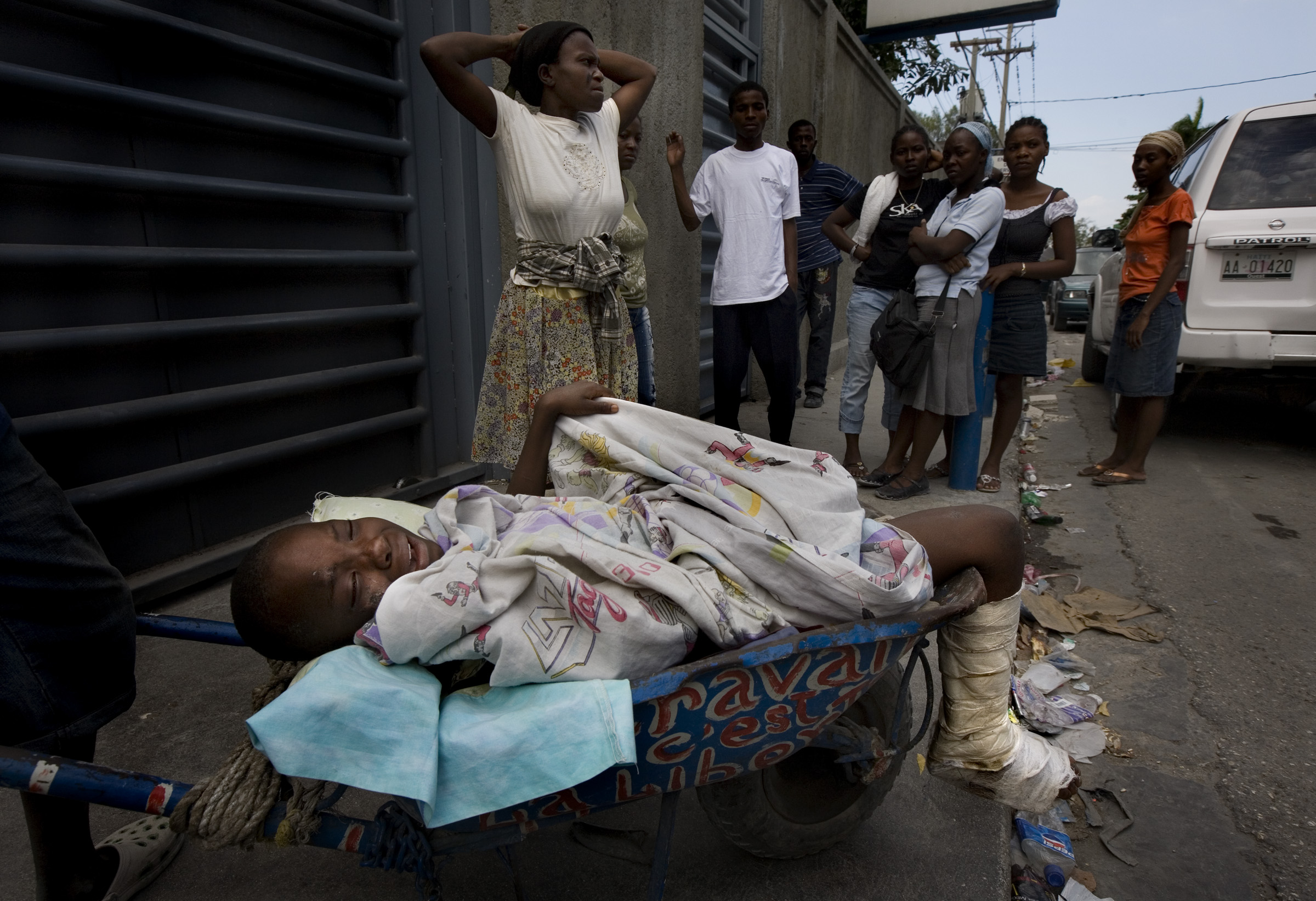 A young boy was carried in wheelbarrow by his family to a clinic for medical treatment outside of Port-au-Prince.