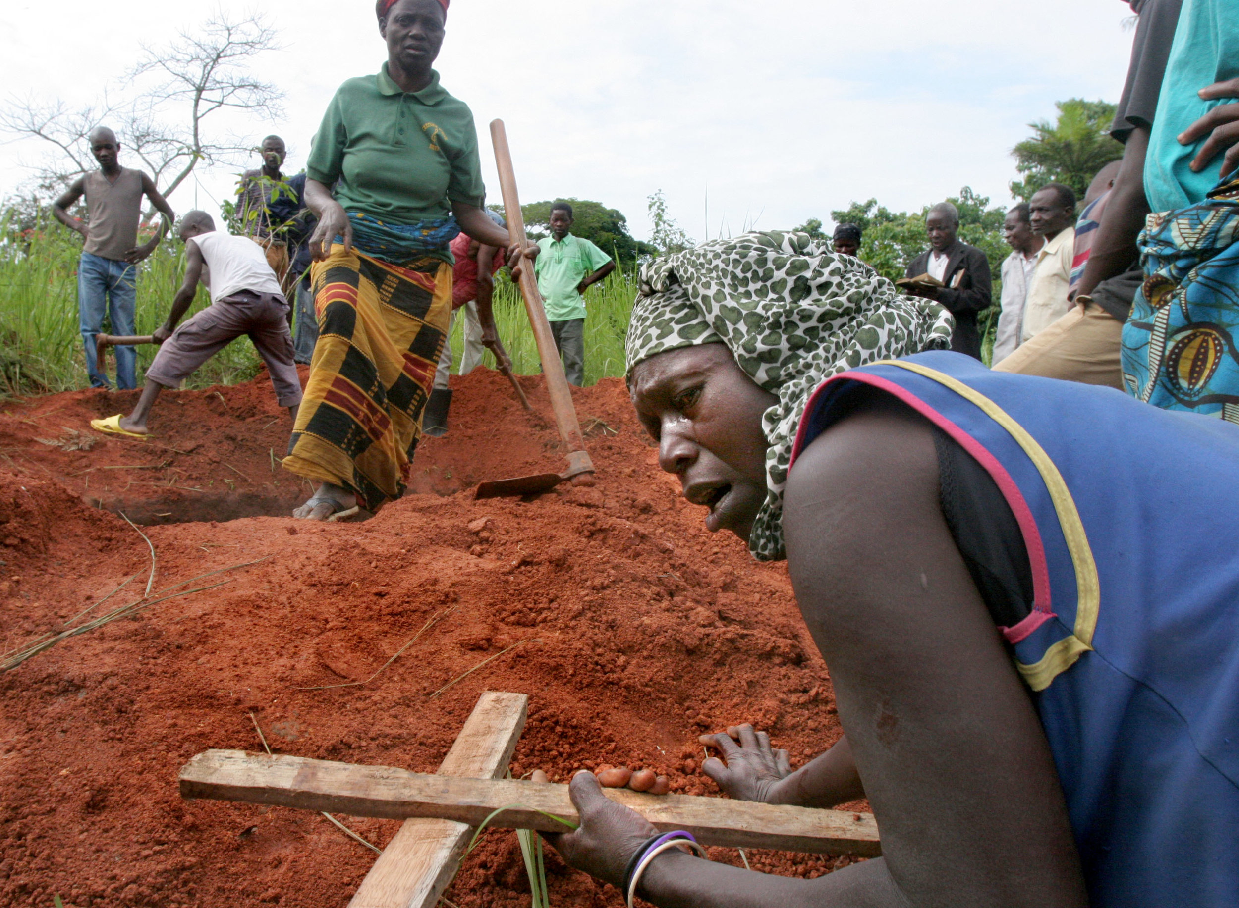 The mother of Louiza Nevish Bati, 23, who died of the Marburg virus in Uige, Angola, collapses on her grave. A cousin of Ebola, the Marburg virus is highly contagious, making any outbreak a cause for widespread fear and fascination in a world shrunk by international travel and trade. Marburg spreads through blood, vomit, semen and other bodily fluids. Even a cough can prove fatal for someone hit by a few drops of spittle. Corpses, teeming with the virus, are especially dangerous. A contaminated surface can be deadly -- the virus can find its way into someone's eyes, nose or mouth, or enter the bloodstream through a cut.