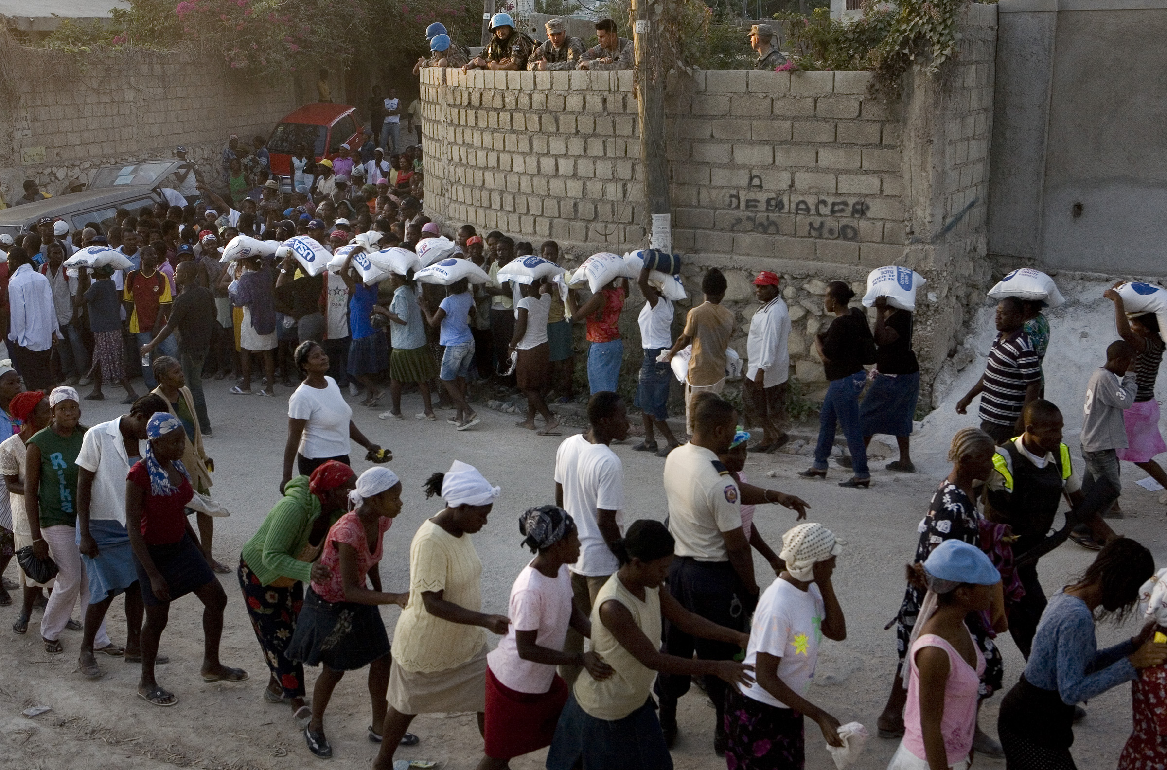Haitians wait to receive rations of rice.