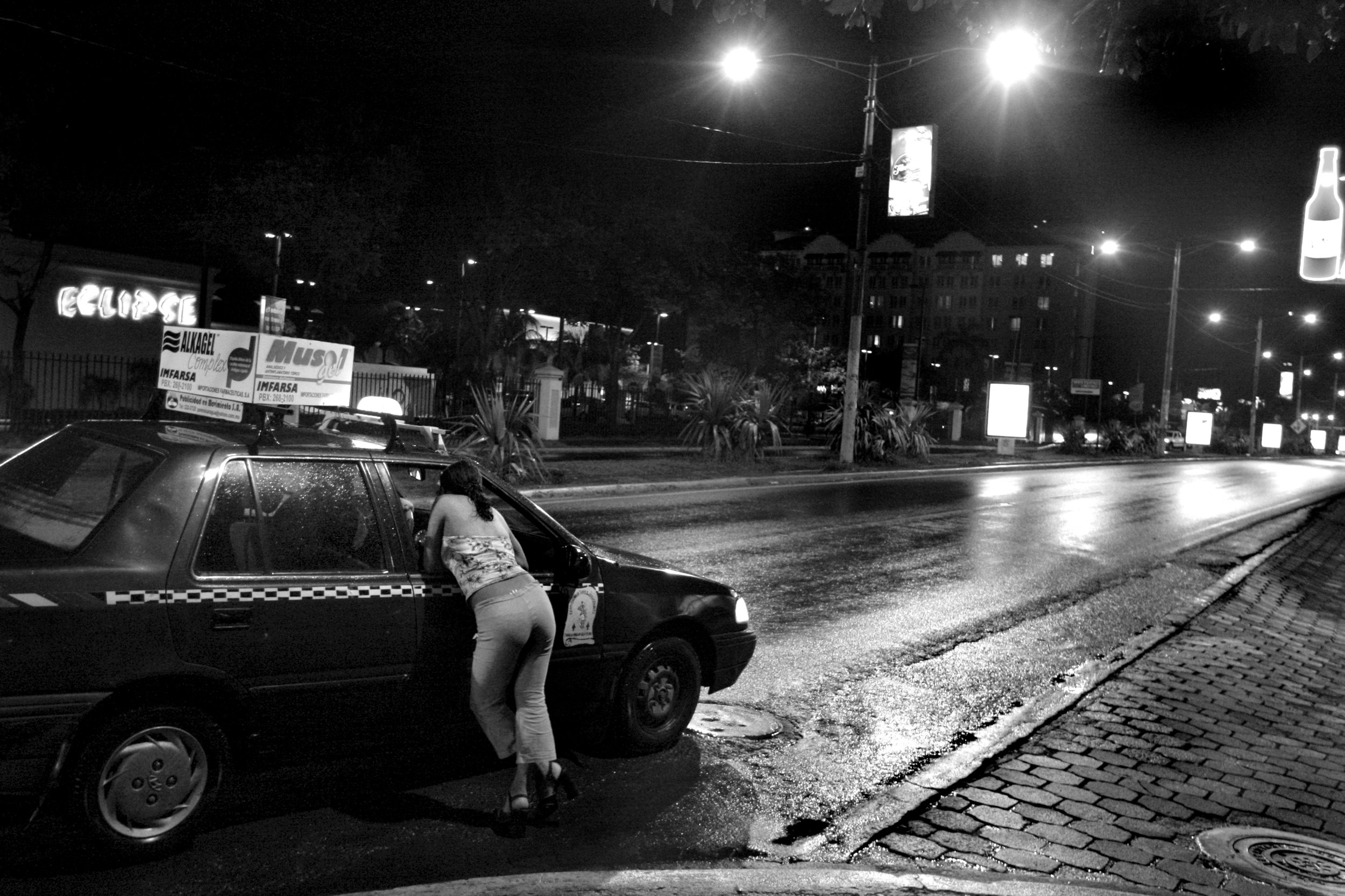 """Ivania Gonzalez, 16, solicits a customer on a main street in downtown Managua. When Ivania was 12, she was raped by a cousin. """"This life is not happy and not nice. I can do it now but probably not later. I don't like this life. It's for money to pay for my classes. In four months I graduate. I'm trying to see if I can buy a small house and make my own beauty business. I want to study computer engineering."""""""