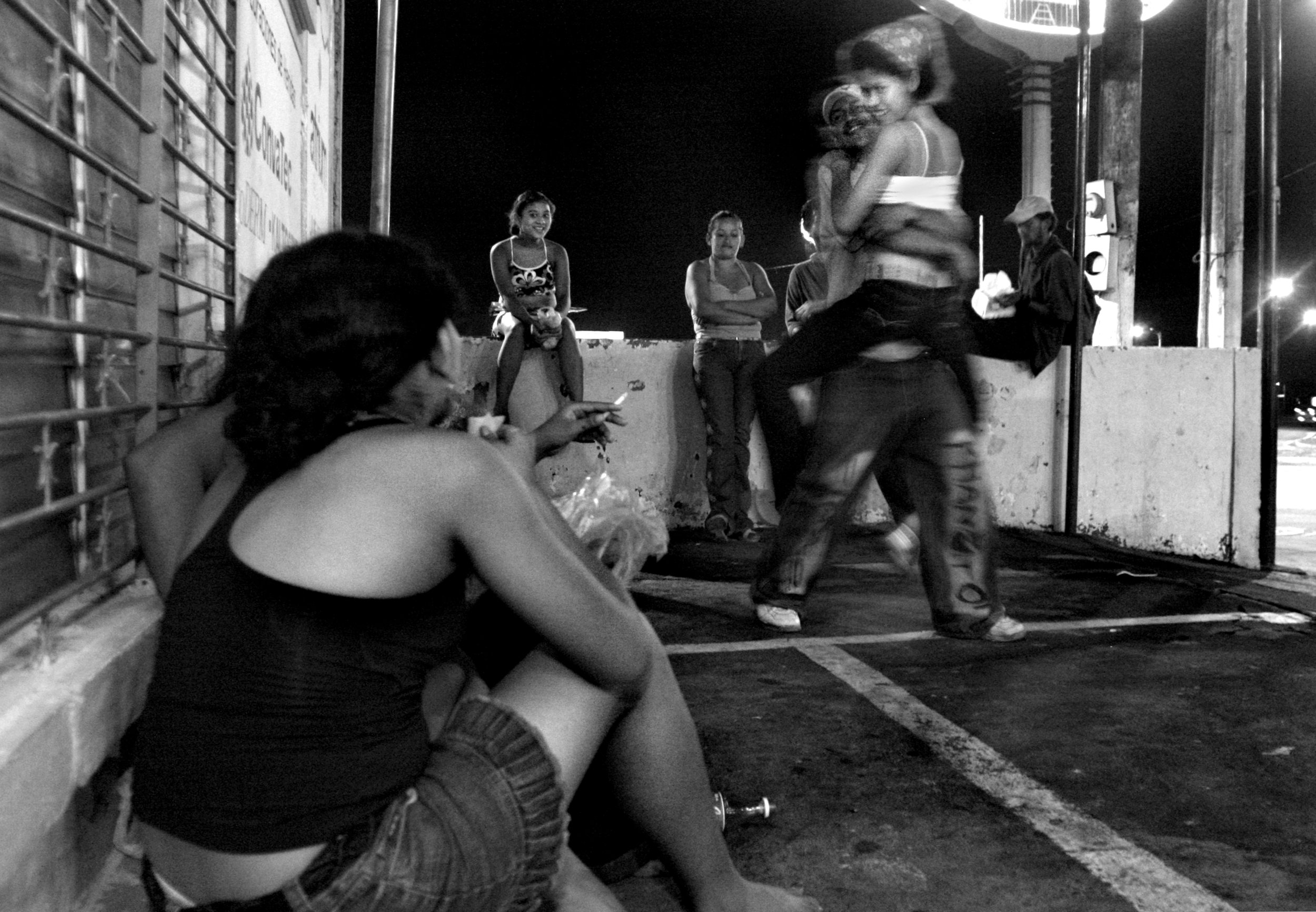 The girls joke around with a group of guys along a main street in downtown Managua.