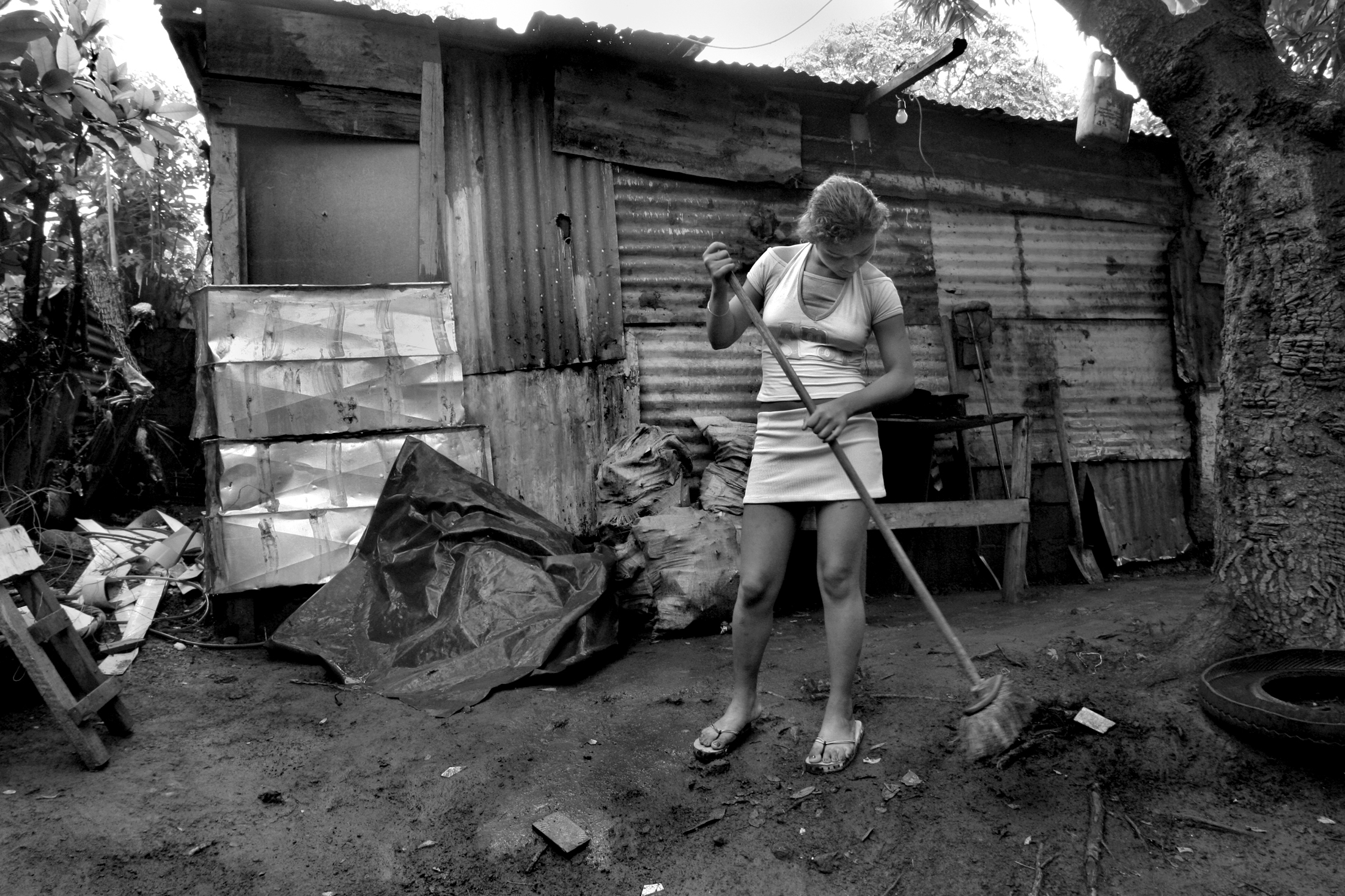 """Meiling, 15, a child prostitute, sweeps outside of her home. """"I'm in the 4th grade and I use the money sometimes to buy my notebooks. I go to the afternoon school shift. We'd all be starving and I'd rather do what I do than see my siblings go hungry."""""""