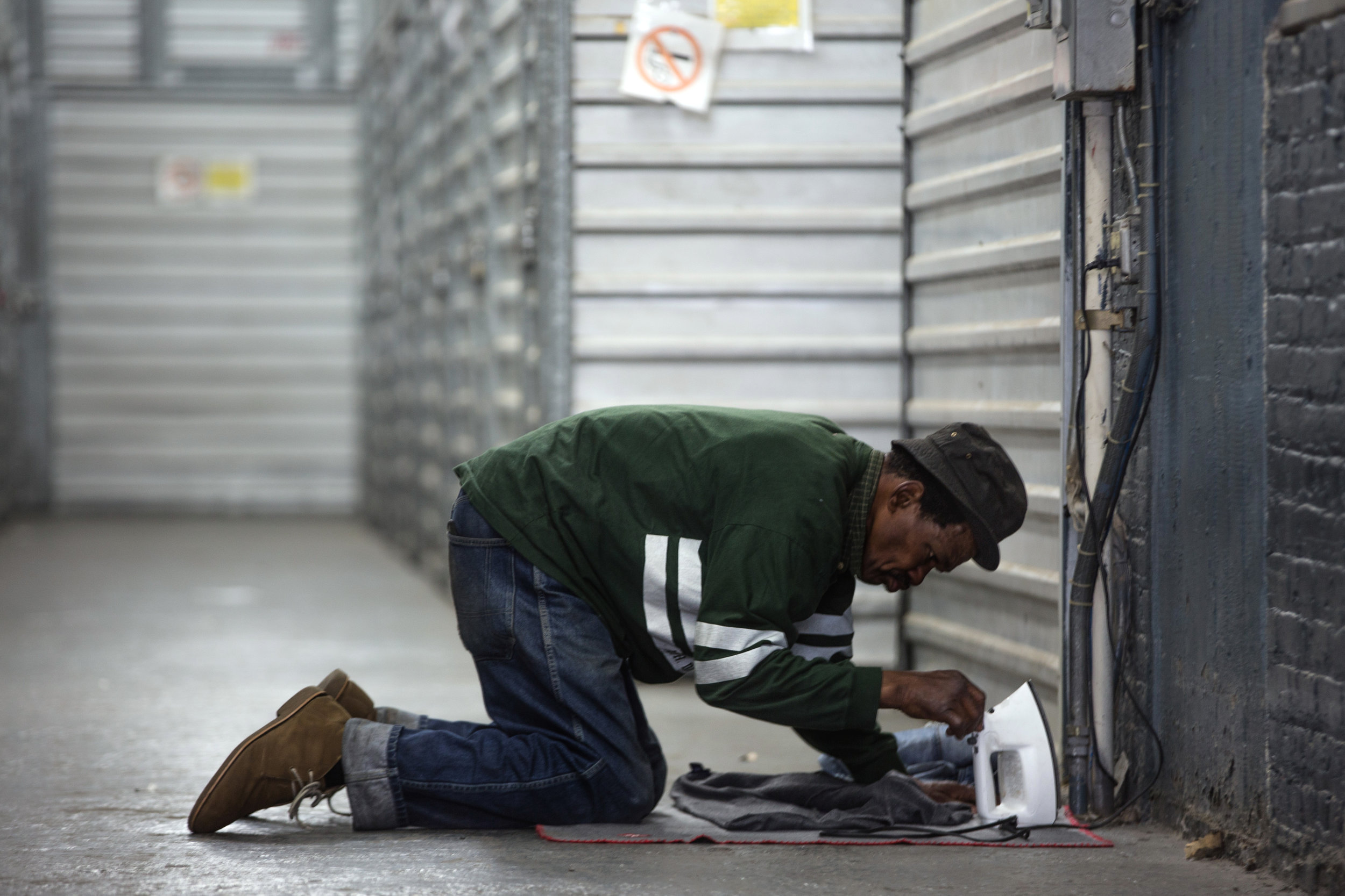 A homeless man (did not want to be identified) uses an electrical outlet to iron his clothes in a hallway between storage units.