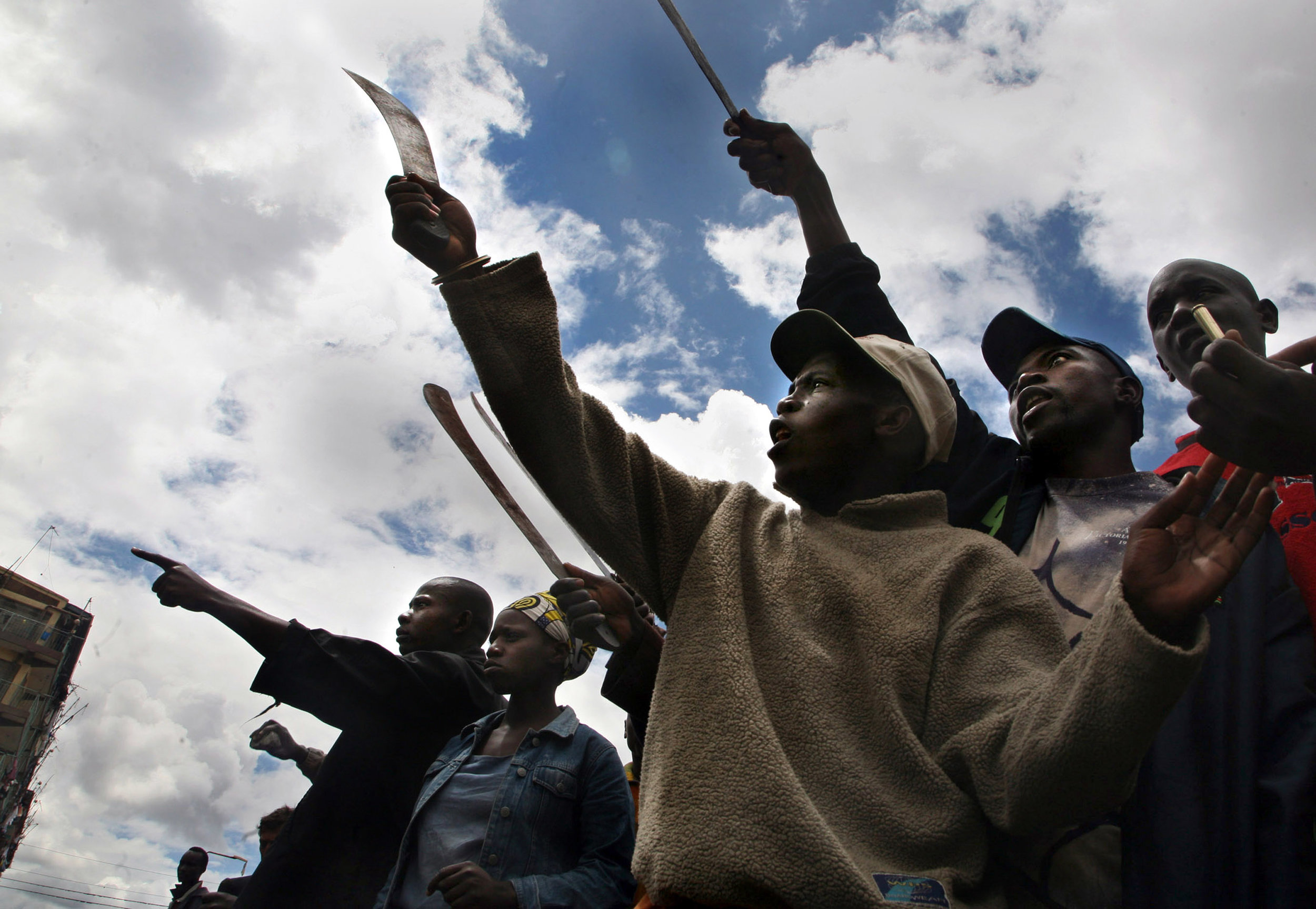 ODM supporters hold machetes, stones, and sticks as they shout towards Kikuyu residents of the Mathare slums during another day of ethnic violence in Kenya. Several homes were set ablaze in Mathare during running battles between Kikuyu and Luo ethnic groups.