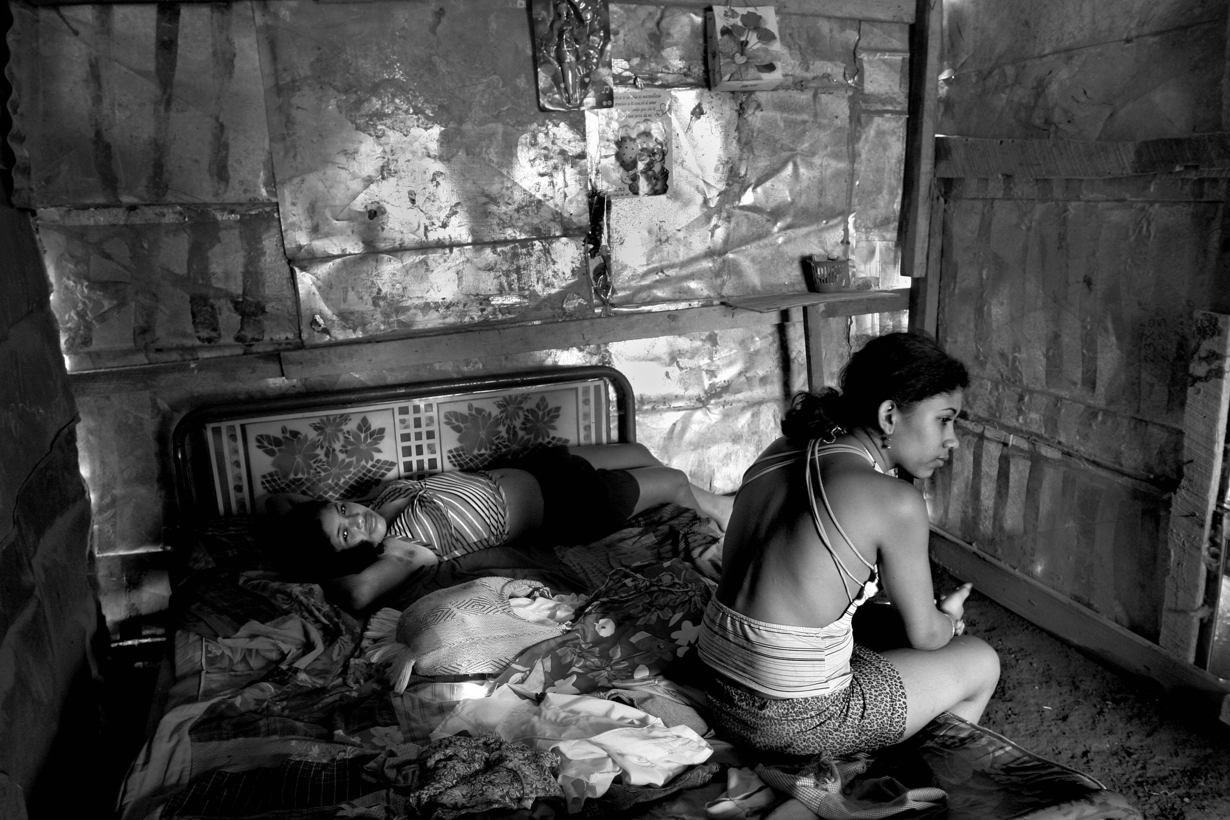 """Ivania Gonzalez, 16, right, and Rozievel, 15, both child prostitutes sit together on the bed in the room they share. Rozievel says, """"Two months after I started working my mother asked me how I got money and I told her. My mom is 60 and a diabetic and she can't work. She agreed there was no other alternative. I finished third grade. I dropped out when we didn't' have any money. I go out every night and I make 100 -150 Cordoba's/night."""""""