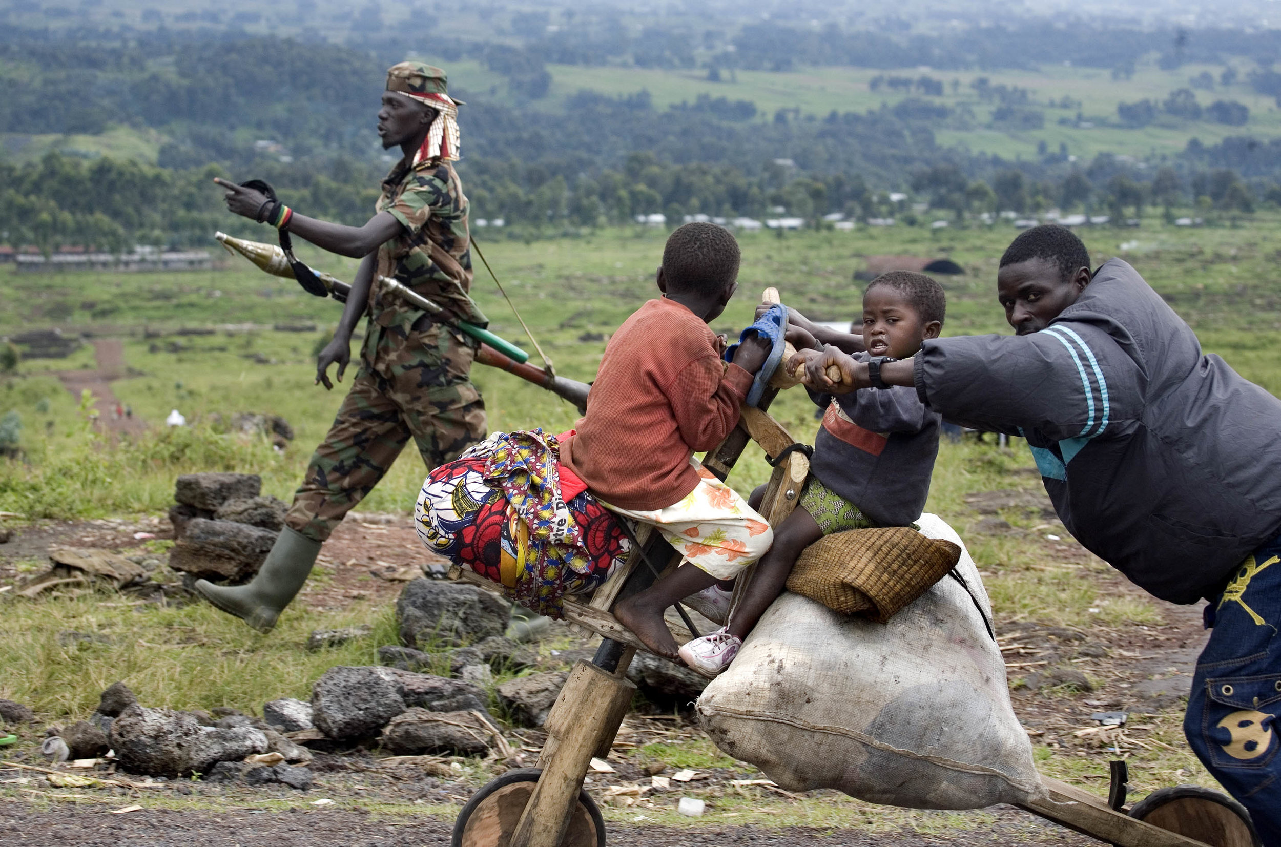 Displaced people returning to their homes outside of Goma walk past a CNDP soldier in rebel controlled territory. Fighting escalated in recent weeks between the rebel group CNDP, the National Congress for the Defense of the People, and the Congolese army, displacing tens of thousands of people.