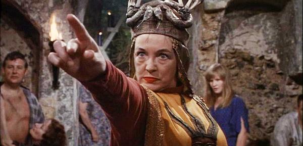 Standbild aus dem Film; Stephanie Bax in ritueller Gewandung hebt gebieterisch den Zeigefinger. Bossy und visionär: die Oberhexe hat ihren Zirkel im Griff.