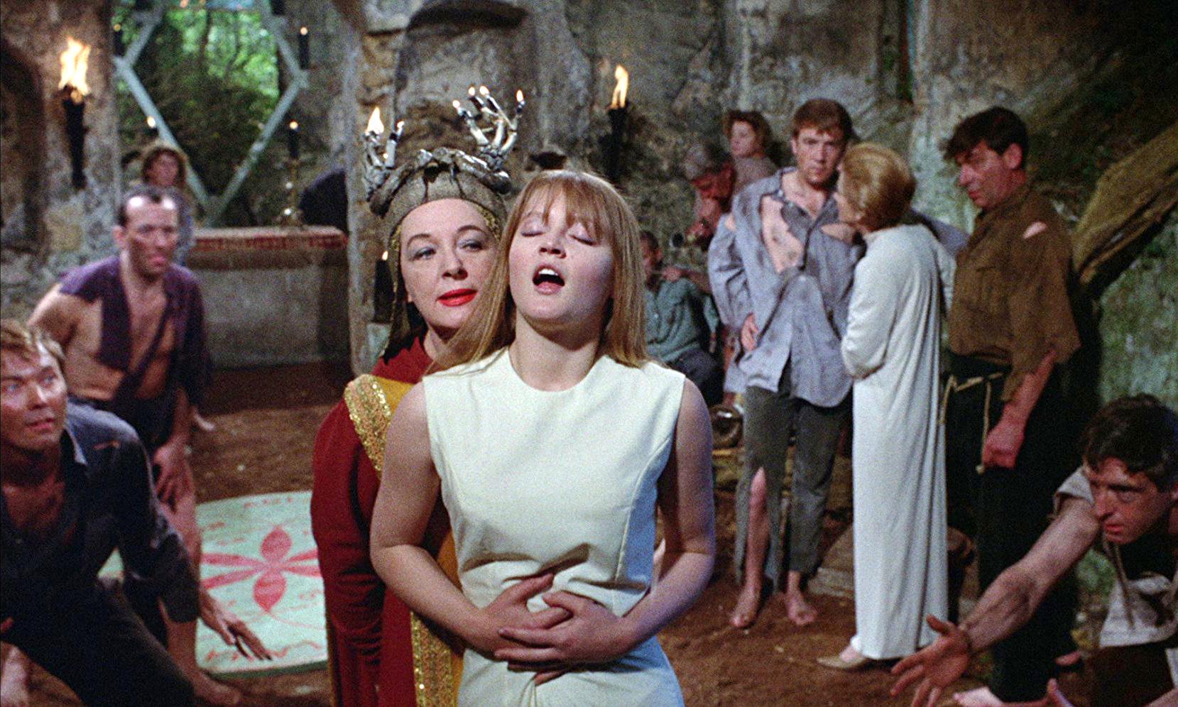 Standbild aus dem Film; Stephanie nähert sich der weiß gekleideten Jungfrau Linda von hinten, diese öffnet entrückt den Mund. Der Hexenzirkel beobachtet die Szene erregt.