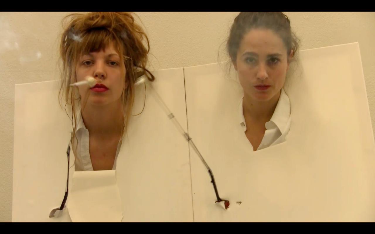 Sophie Schmidt und Sophia Mainka haben weiße Leinwände mit ihren Köpfen durchlöchert und rauchen Zigaretten ohne Hände mit einer speziellen Halteapparatur.