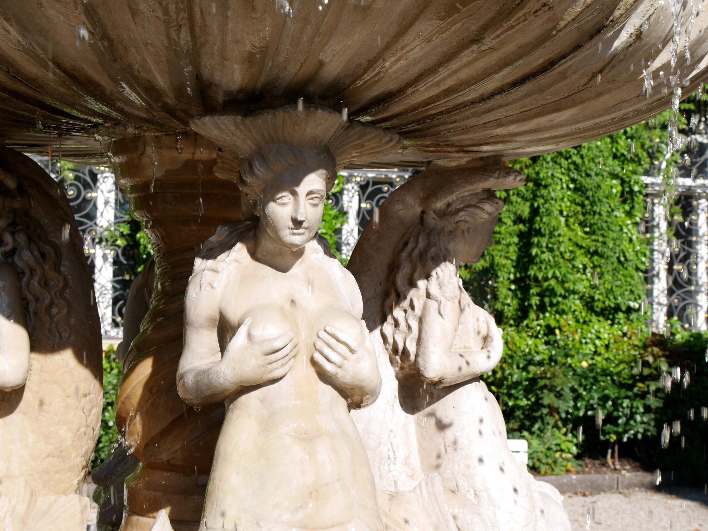 Sonnenschein und Brunnen mit weiblichen Figuren, die ihre Brüste in die Hand nehmen. Einer der Innenhöfe der Evangelischen Akademie in Tutzing.