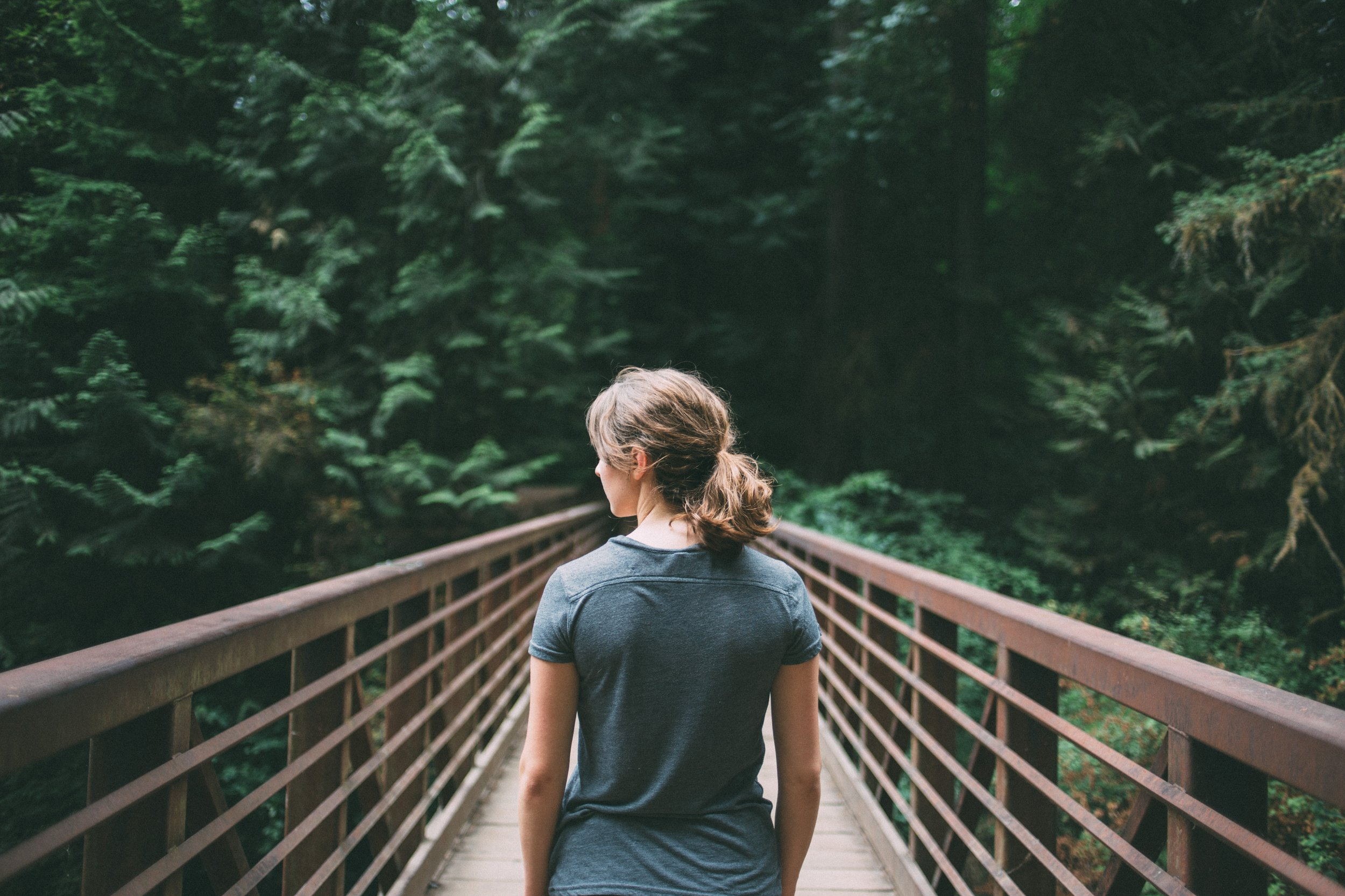 woman on bridge in a forest