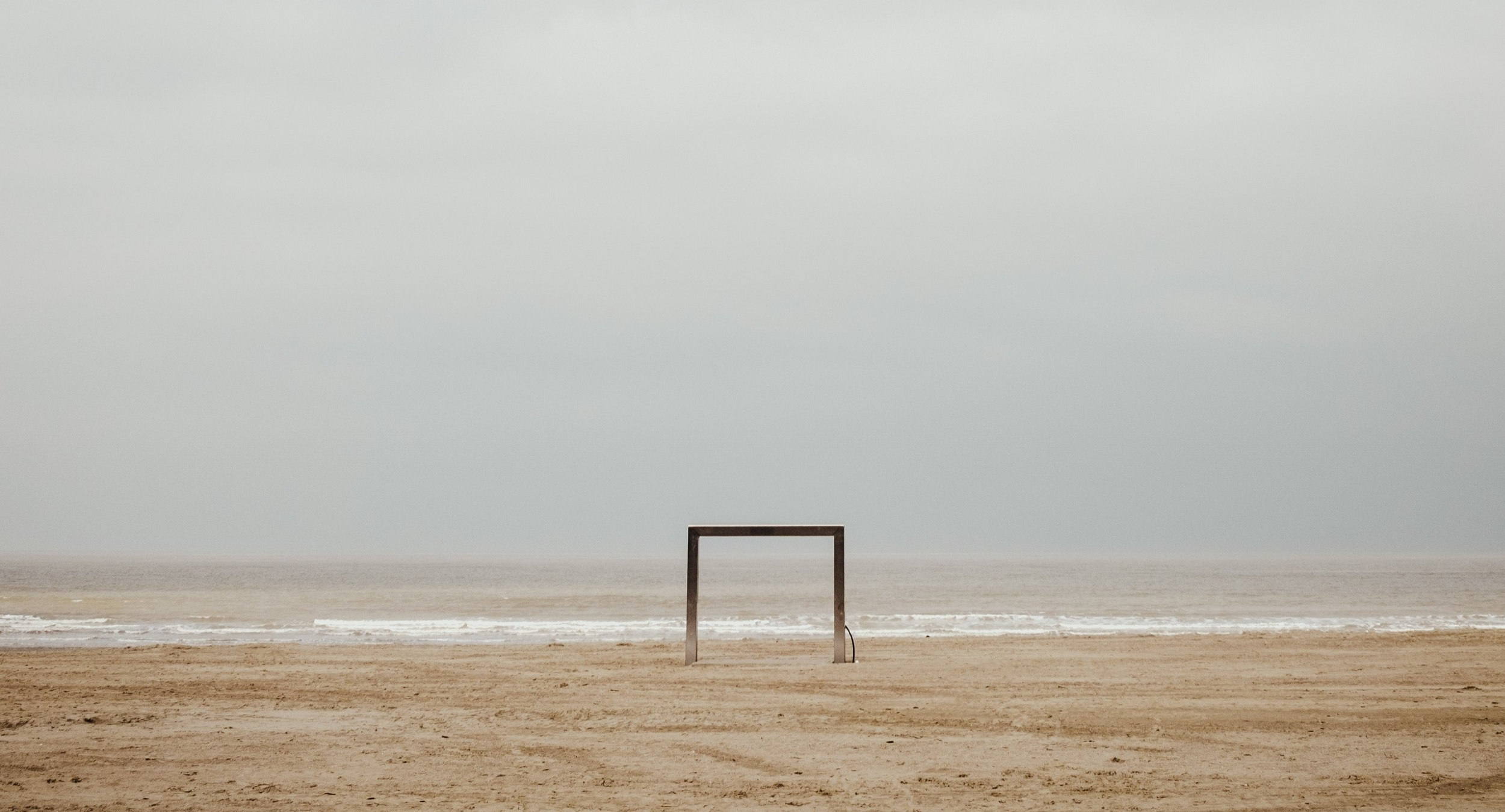 cloudy sky, wooden frame on an empty beach