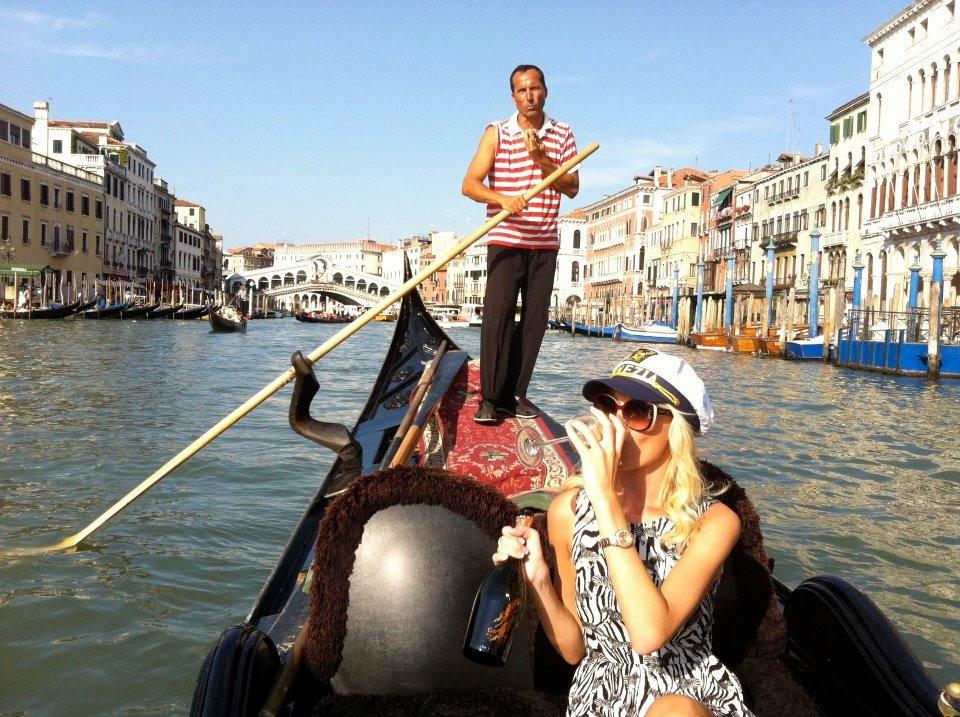 Travel Blogger Katy Johnson sips wine in the Grand Canal, Venice, Italy.