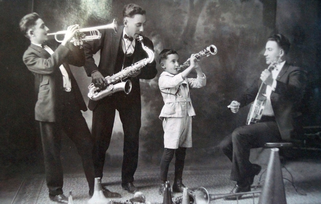 DeGrazia playing trumpet on the left, with his brothers and a friend. He paid his art studies performing in muisc halls.