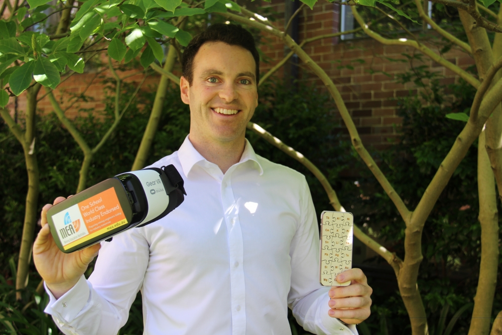 James Tibbett holding the virtual reality headset and the 'smartphone' puzzle.