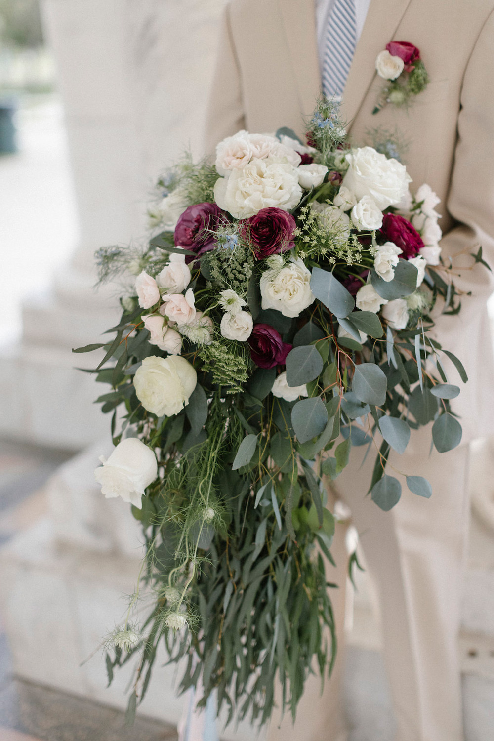 Groom with boutineer holding bride's over-sized cascade bouquet - fresh flowers