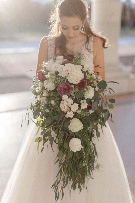 Bride admires her over-sized cascade bouquet - fresh flowers