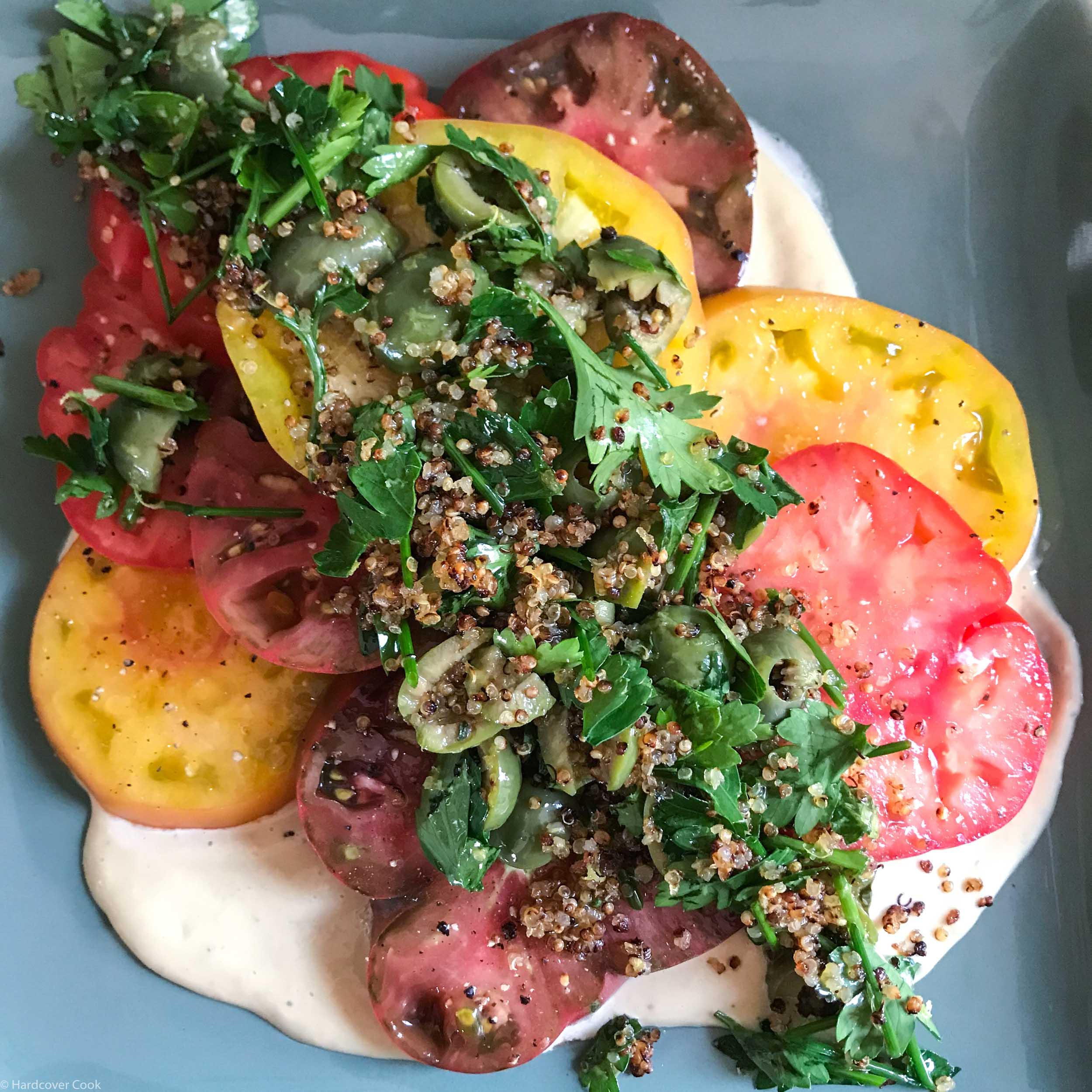 Heirloom Tomatoes with Crushed Olives, Crispy Quinoa, and White Anchovy Dressing from Poole's Diner Cookbook