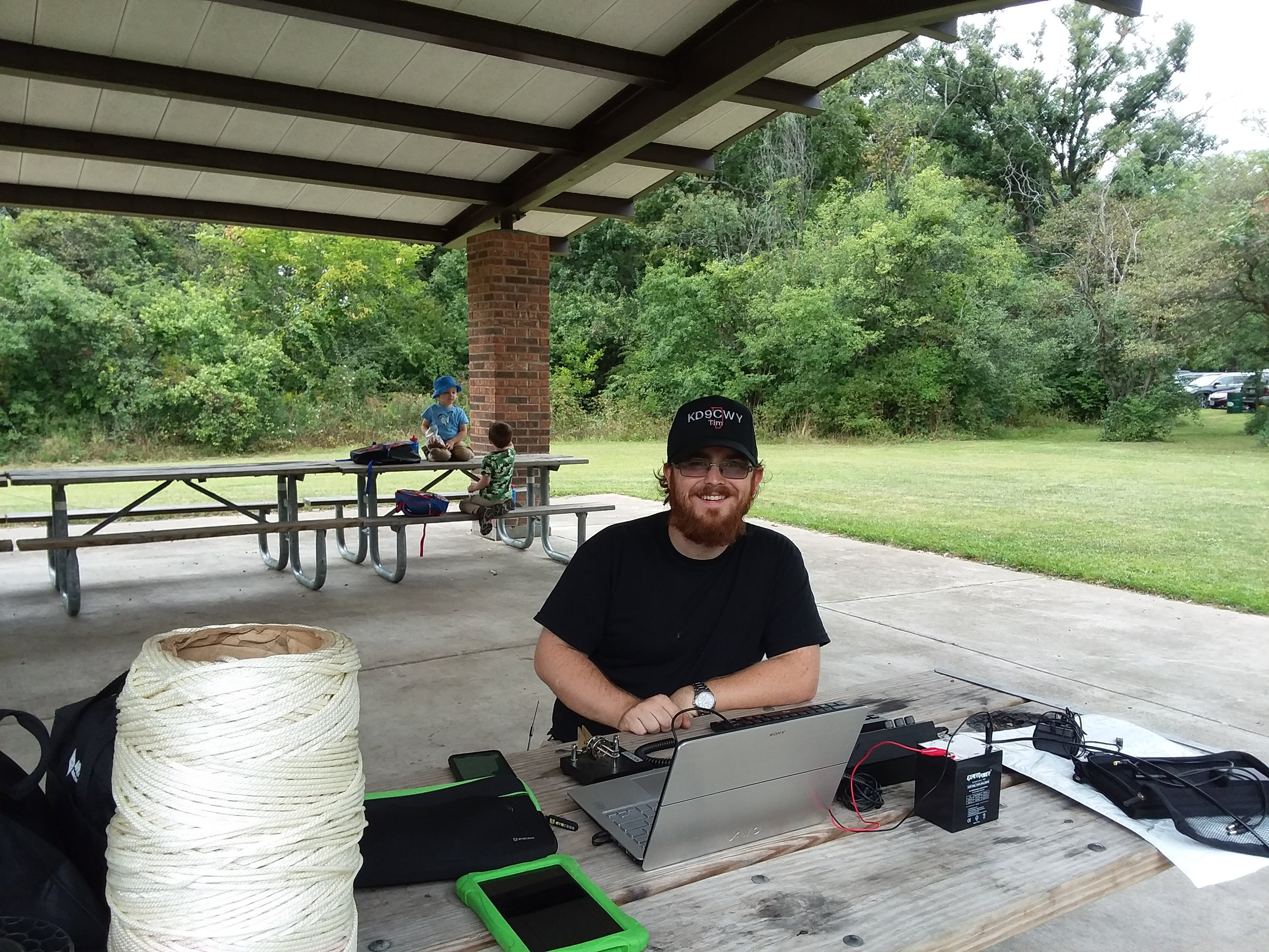 """Tim (KD9CWY) with his set-up, and his sons Archer and Hunter (the future """"Super Hams"""") in the background."""