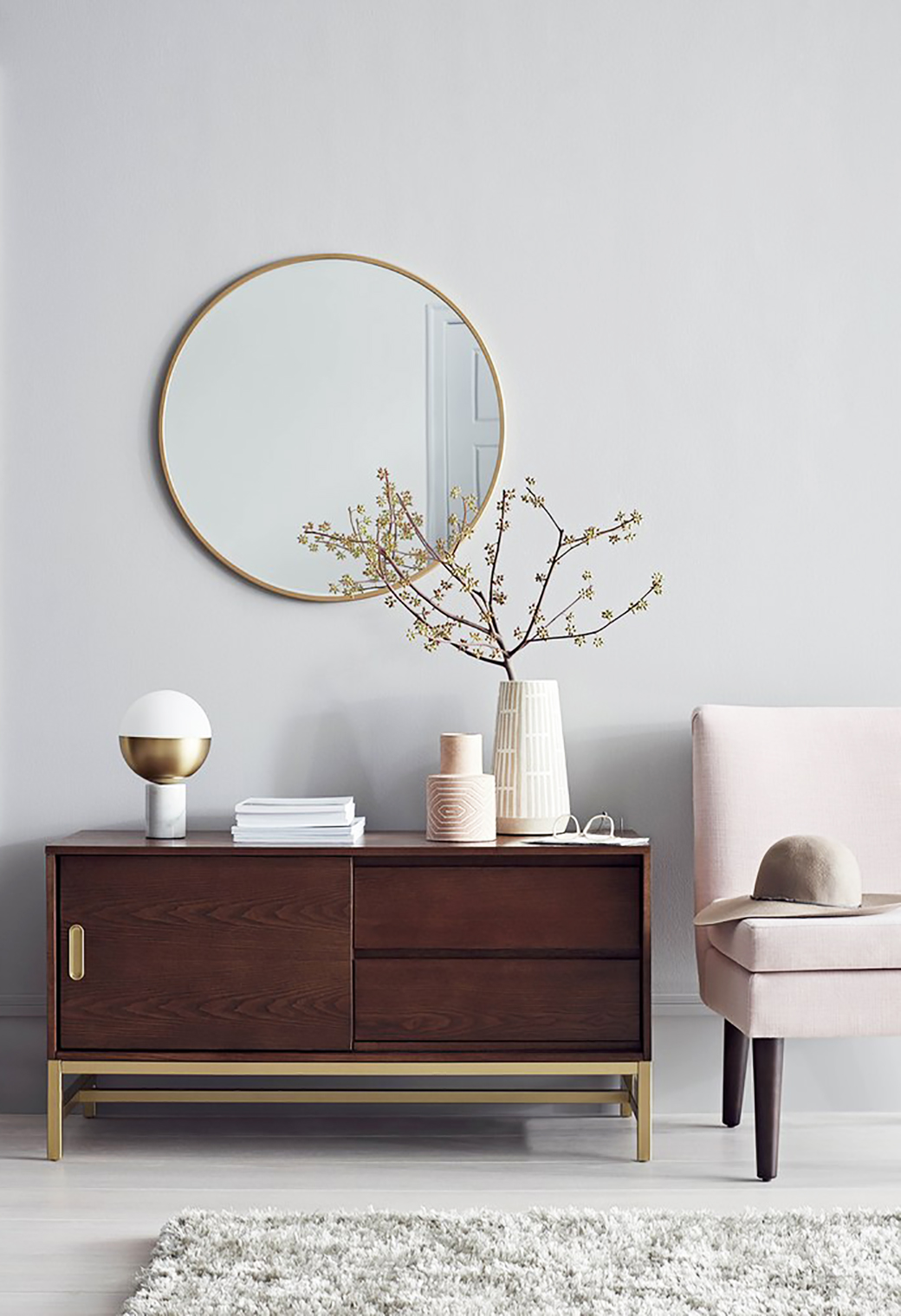 Sideboard with brass accent, ceramic vases, lamps, brass mirror and the Plymouth chair in blush pink.