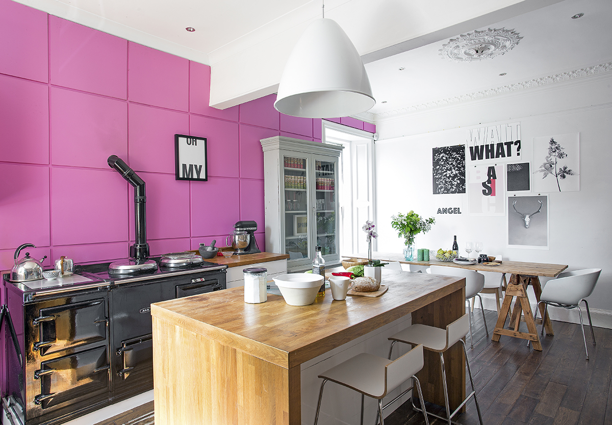 The shocking pink MDF paneling is painted in 'Flamingo' by Dulux. The pendant light above the island unit was an investment buy from Best Lite.
