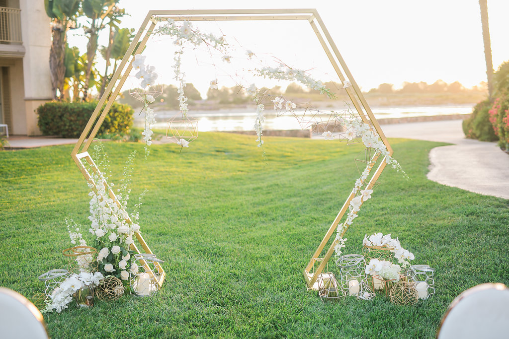 The stunning gold hexagon ceremony arch by Enticing Tables was completed the night before the shoot. Delicate hanging geometric shapes and floral accents softened the arch and add detail.