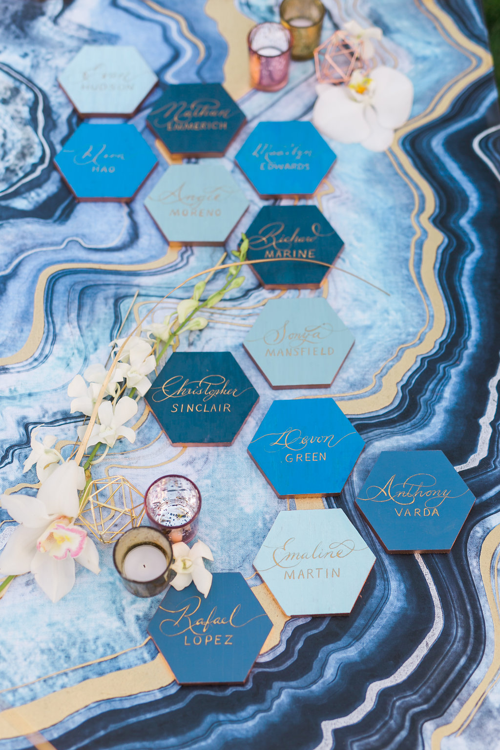 The escort cards were a favorite project and started with gray hexagon tiles that I painted in different shades of blue and gold paint around the edge. The look was completed with beautiful hand painted calligraphy by Olivia of Handcrafted Occasions with a marble like blue and gold canvas painting as a backdrop.