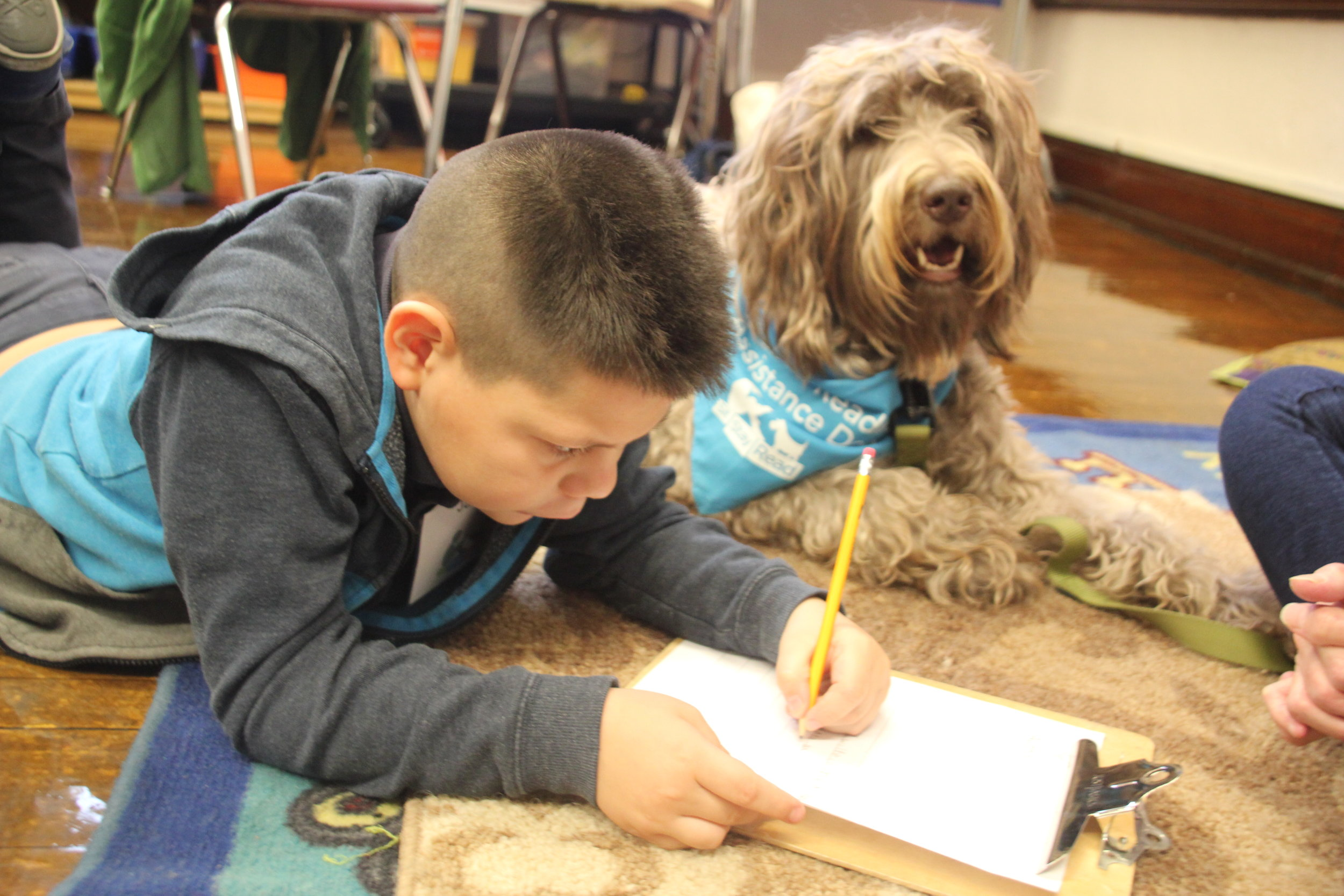 Second-grader Jario eagerly writes his story with the help of Certified Reading Assistance Dog Sylvia.