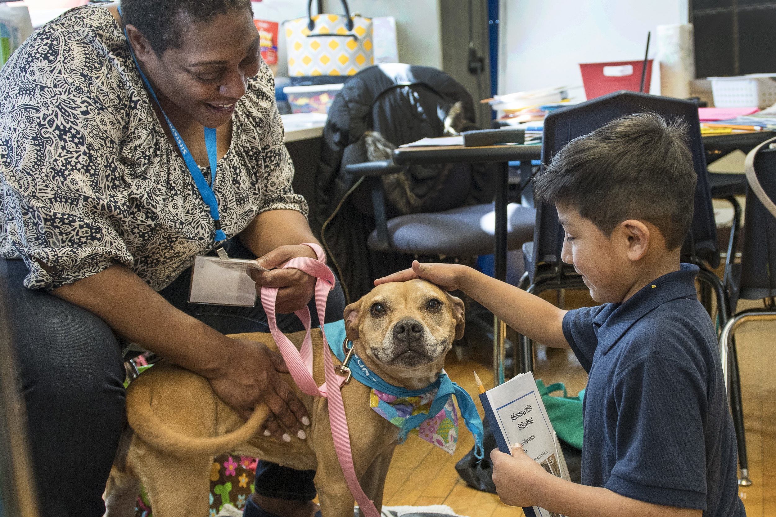 Dog Team volunteer Ms. Lisa and her Certified Reading Assistance Dog Allie listen to second-grade student Inez read one of her stories out loud. (J. Sall)