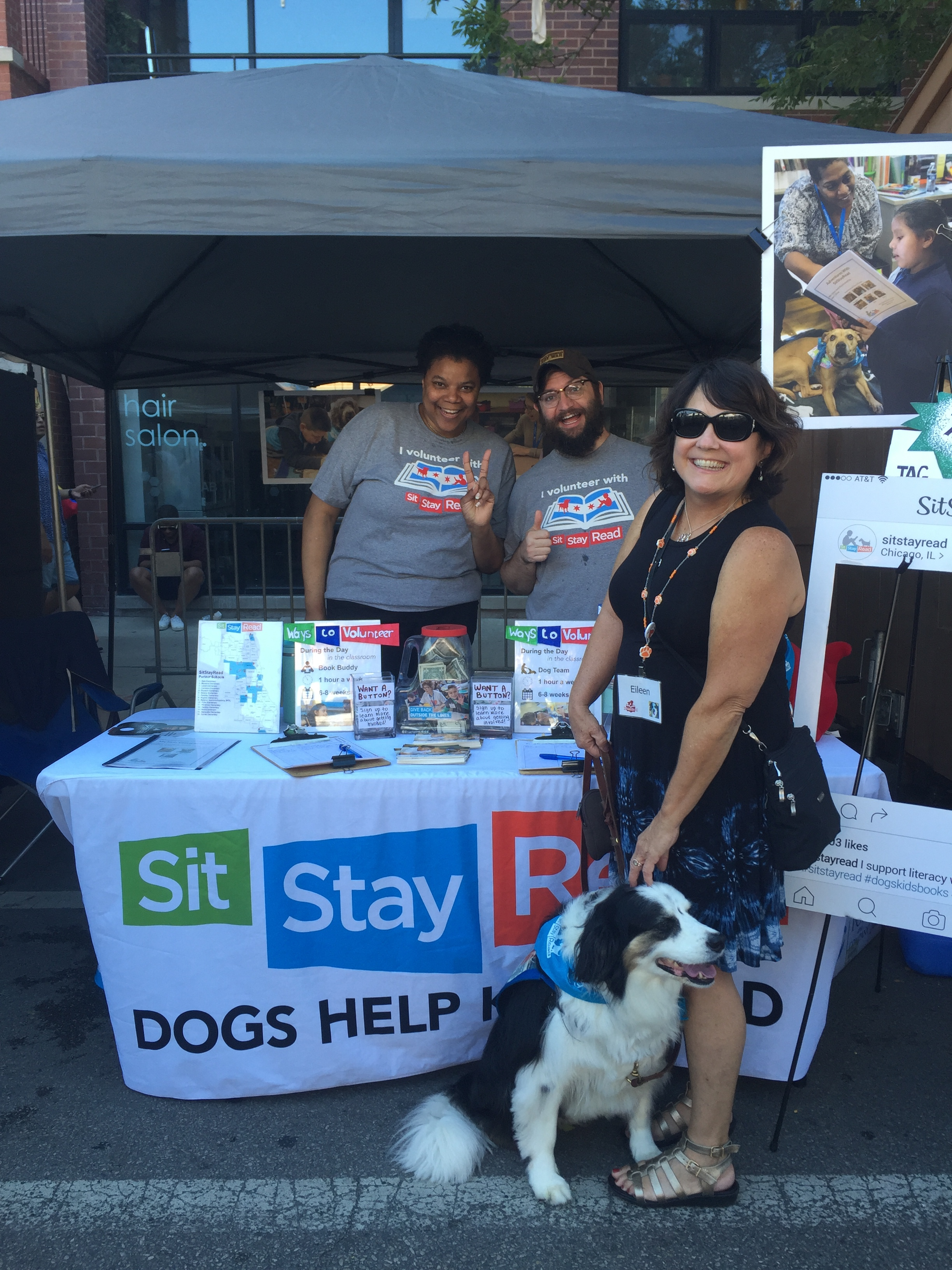 Event volunteers Adrienne and Jeff and Dog Team Eileen and Bandit pose in front of the SitStayRead booth at Market Days. (V. Luisi)