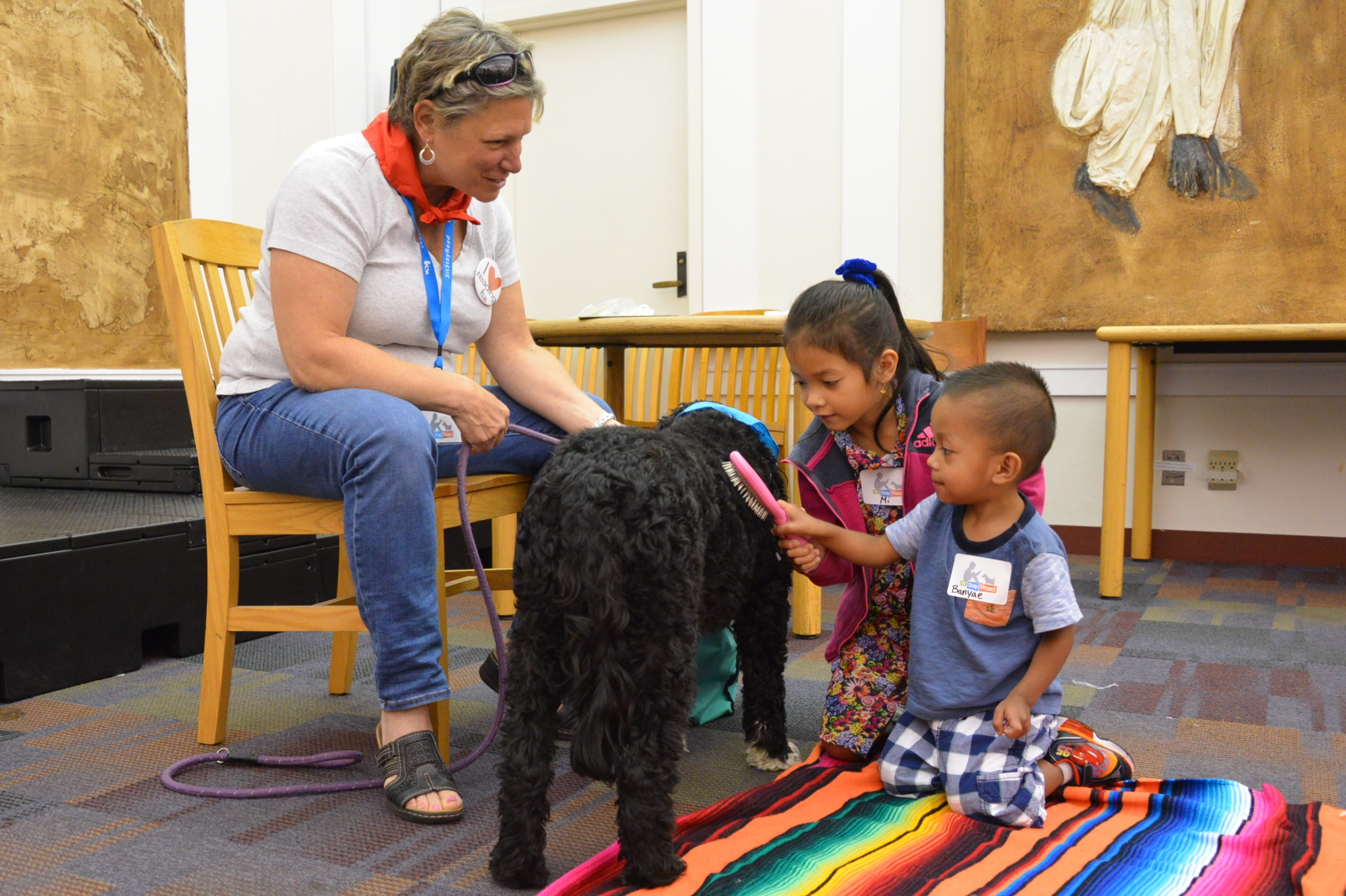 Students Bayne and Mi learn more about brushing Macy from Dog Team volunteer Sue.