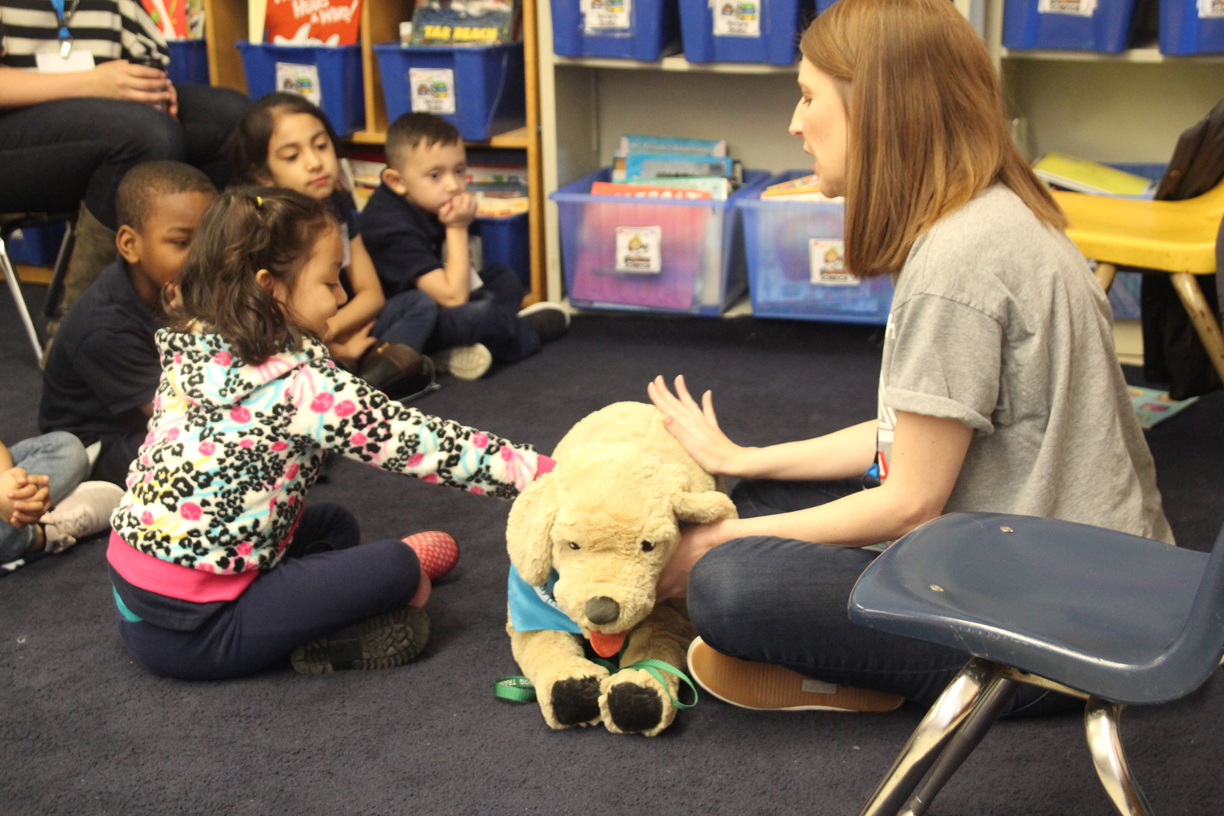 Program Leader Jamie teaches a Kindergarten student how to pet a dog safely using a stuffed animal in the SitStayRead Kindergarten program. (M. O'Brien)