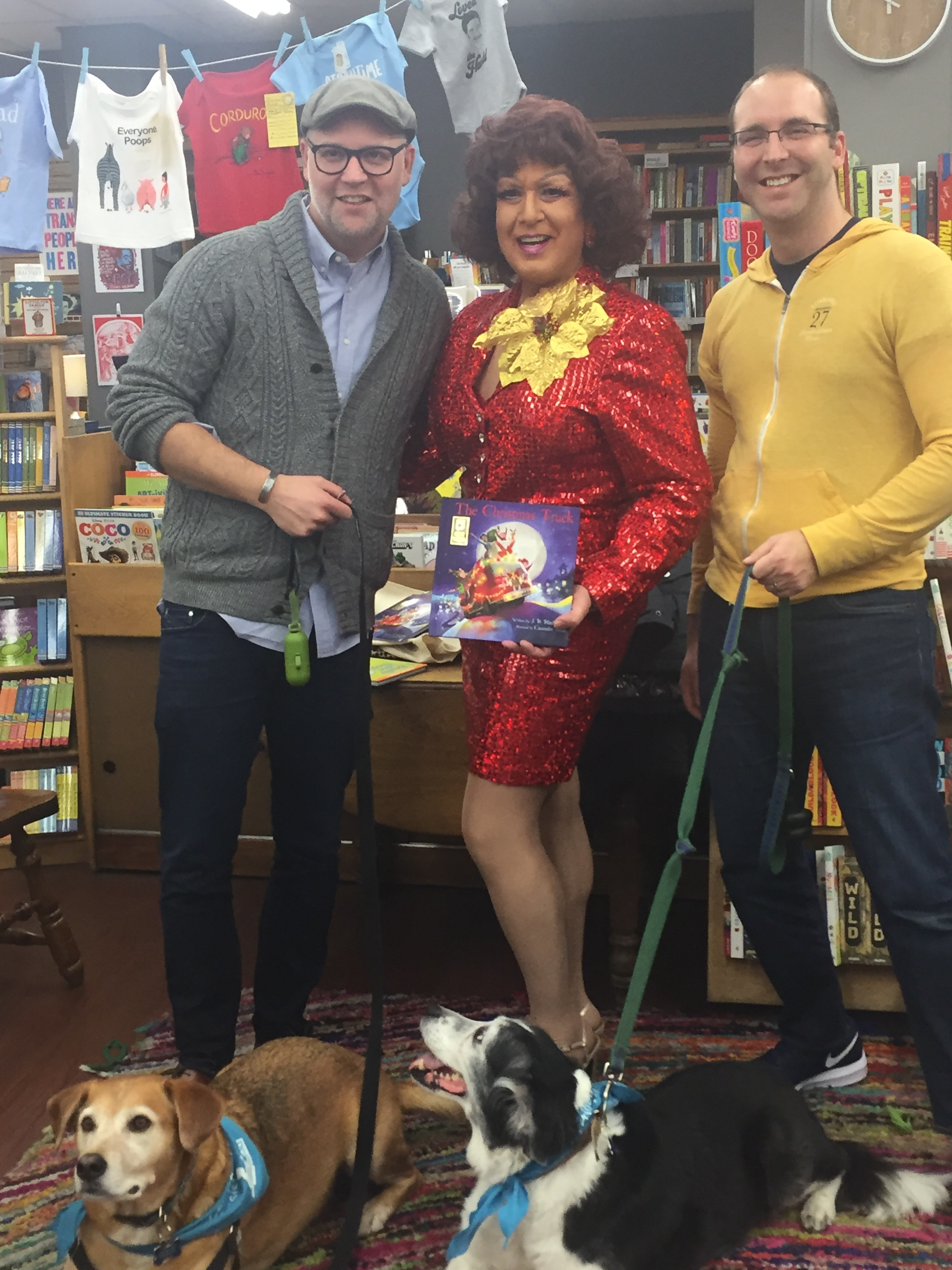 SitStayRead Board Members Bradley Blankenship and Tony Saracco with their Certified Reading Assistance Dogs Cosi and Tilly pose with drag queen Ashley Morgan at the Women & Children First Wishing Tree Read Aloud. (V. Luisi)