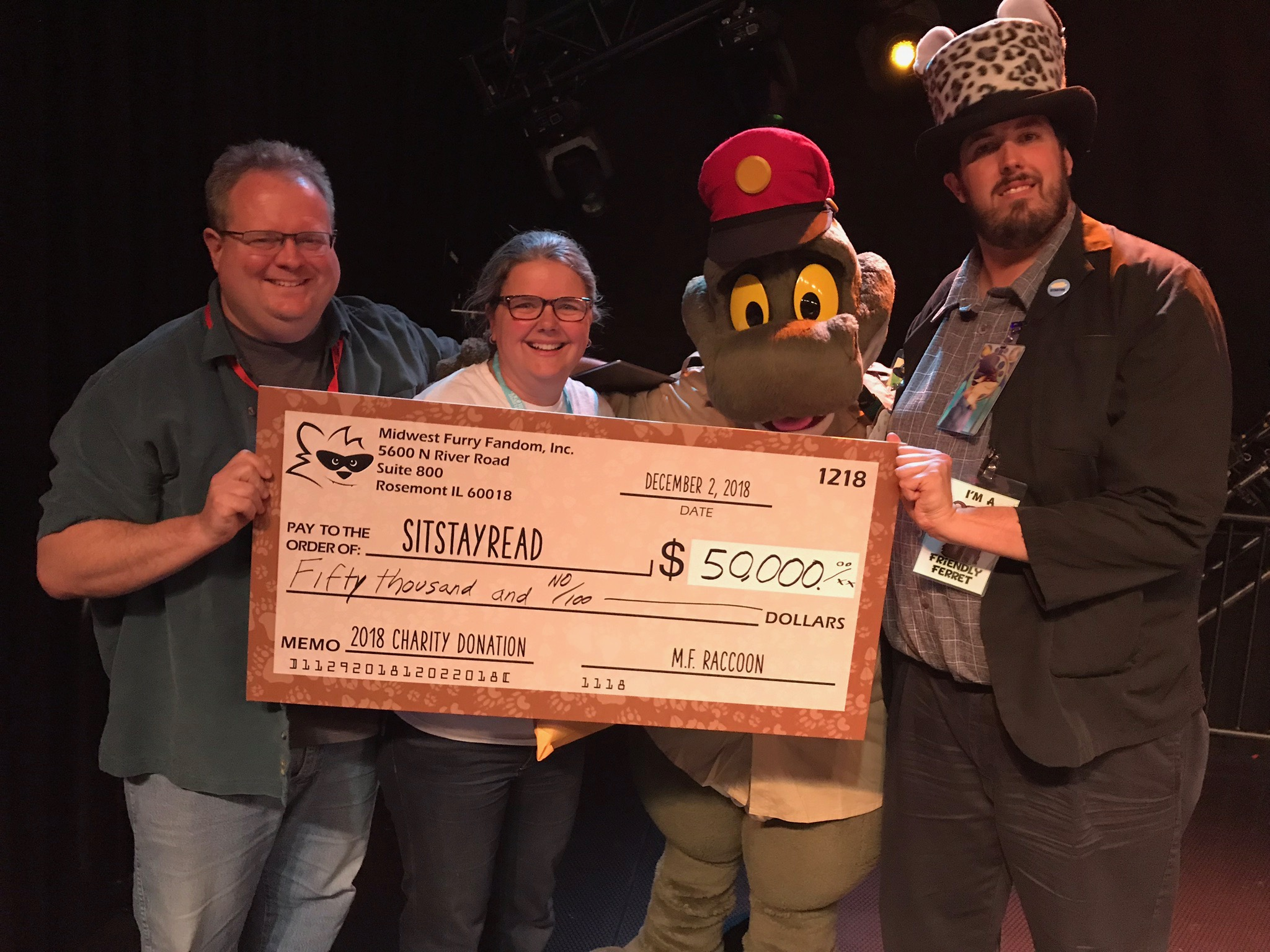 Executive Director Mara O'Brien accepts a check for $50,000 from the Midwest FurFest.