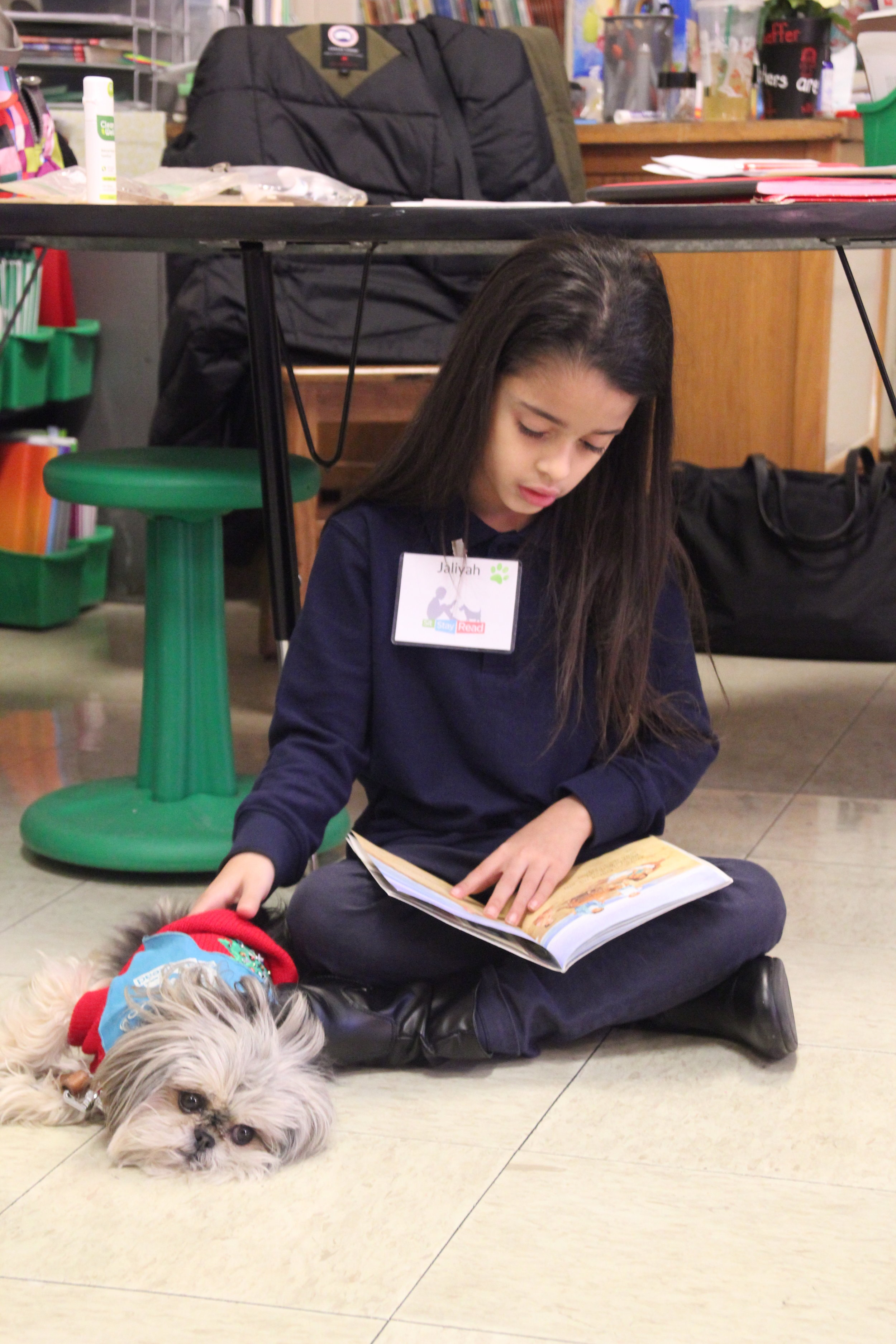 Second-grader Jayilah reads out loud to Certified Reading Assistance Dog Bambi during a SitStayRead Tail Blazers program.